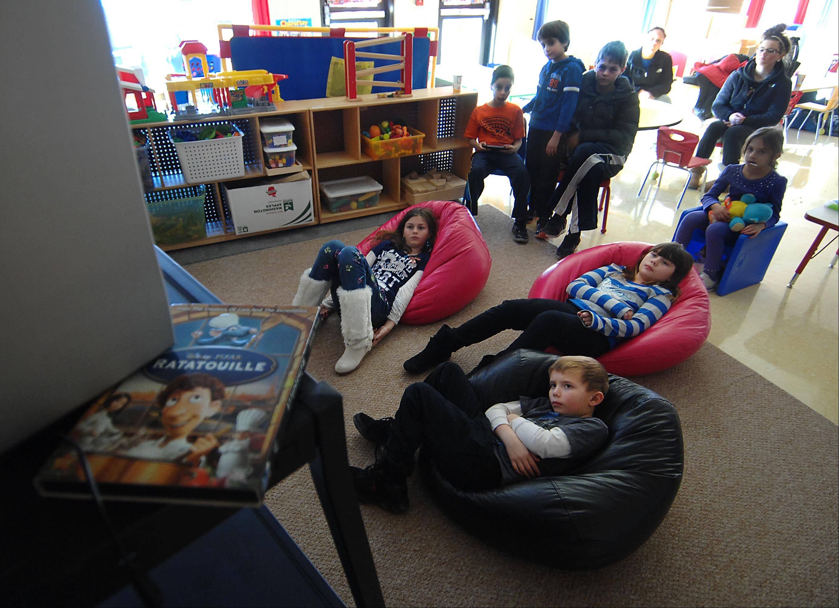 Children Lounge On Bean Bag Chairs As They Watch A Movie At A Parks And  Recreation