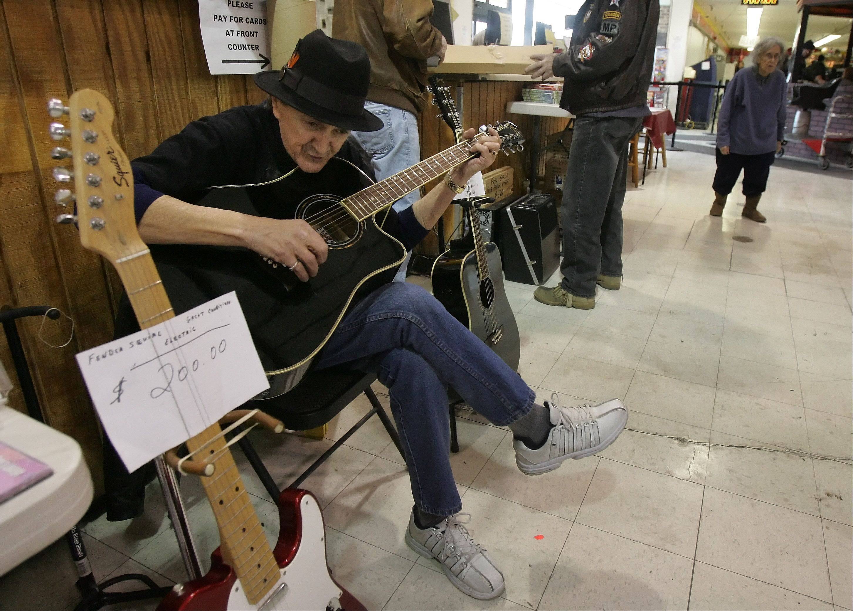Noel Rivera, of Arlington Heights, entertains with his guitar as customers check out the deals at Wolff's Flea Market in Palatine. The indoor location is open every Saturday and Sunday from 8:00 a.m. - 4:00 p.m.