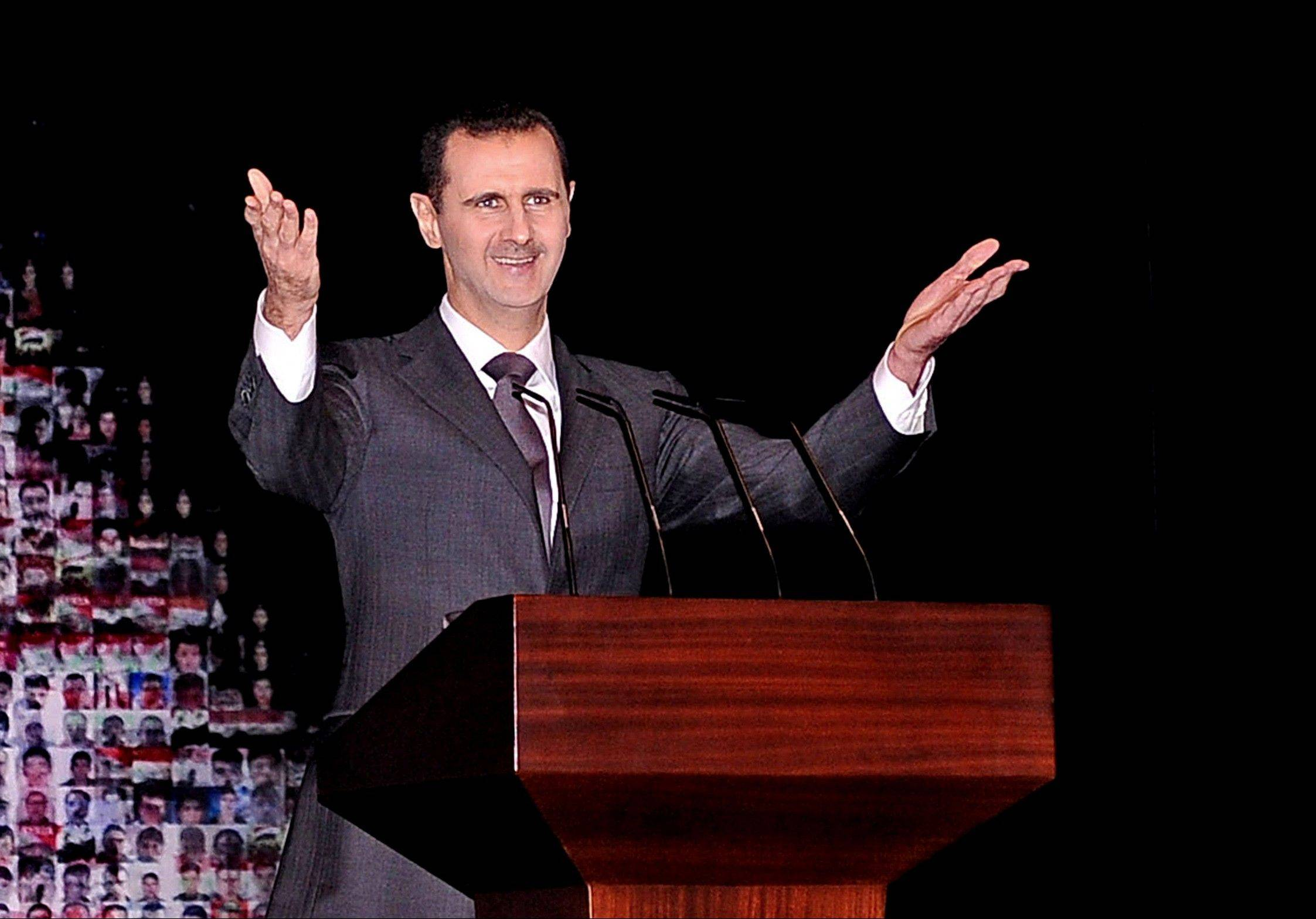 Syrian President Bashar Assad speaks at the Opera House in Damascus on Sunday. He outlined a new peace initiative that includes a national reconciliation conference and a new government and constitution but demanded regional and Western countries stop funding and arming rebels first.