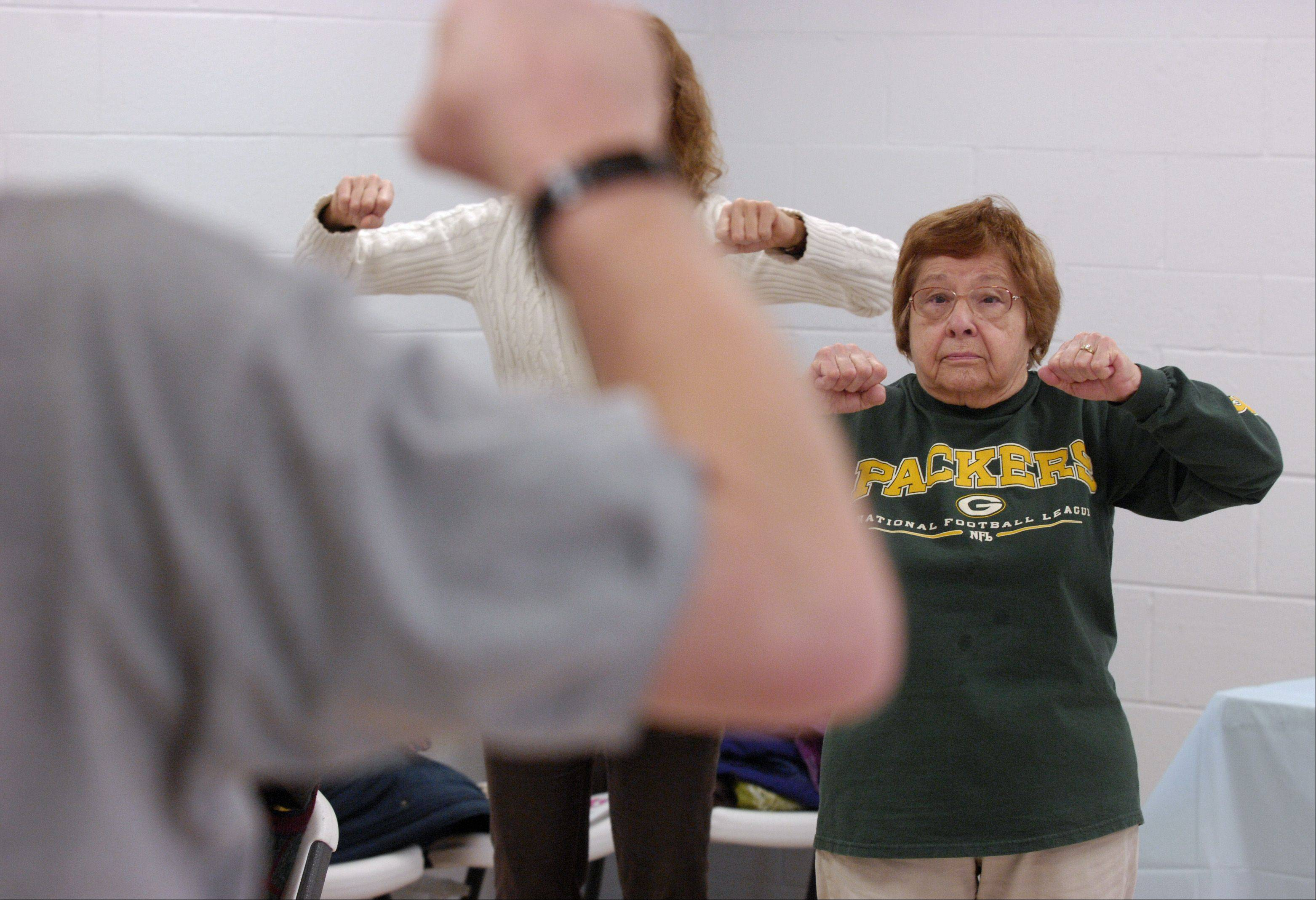Ruth Girard of Lombard tries out Tai Chi during a class with John Robertson at Lombard Park District's Health Fair and Fitness Expo Sunday at the Sunset Knoll Recreation Center.