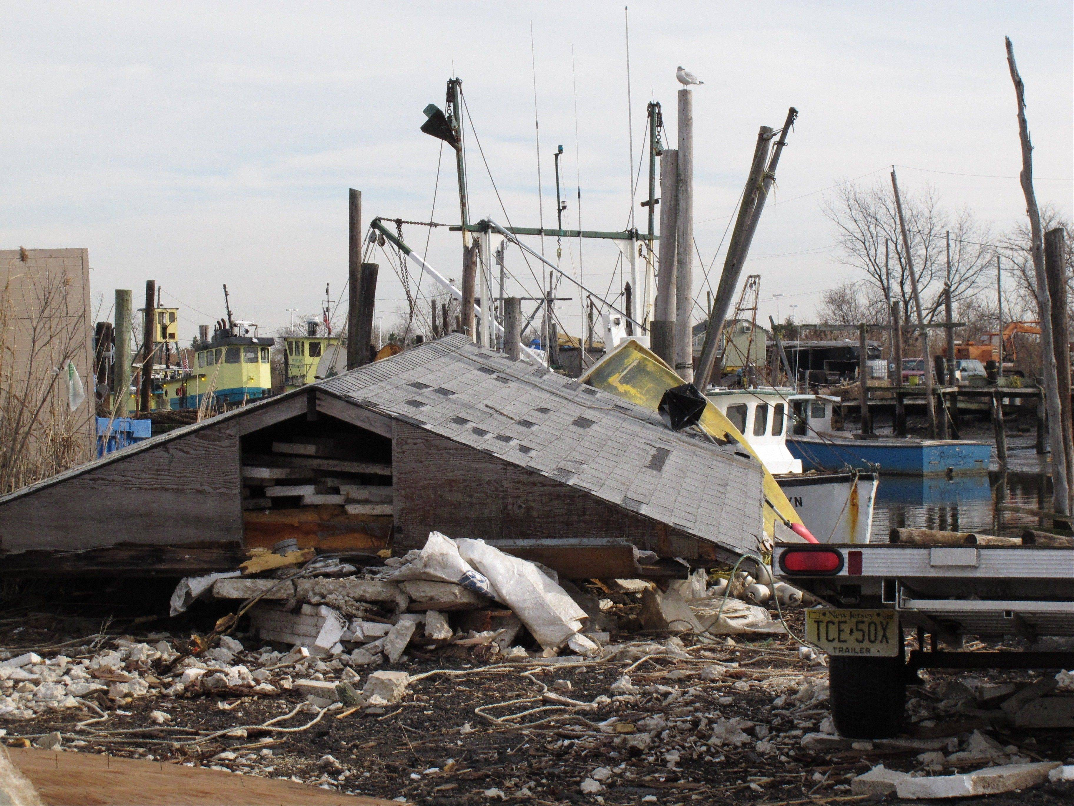 The roof of a destroyed building at the Belford fishing port in Middletown N.J., sits next to a dock.