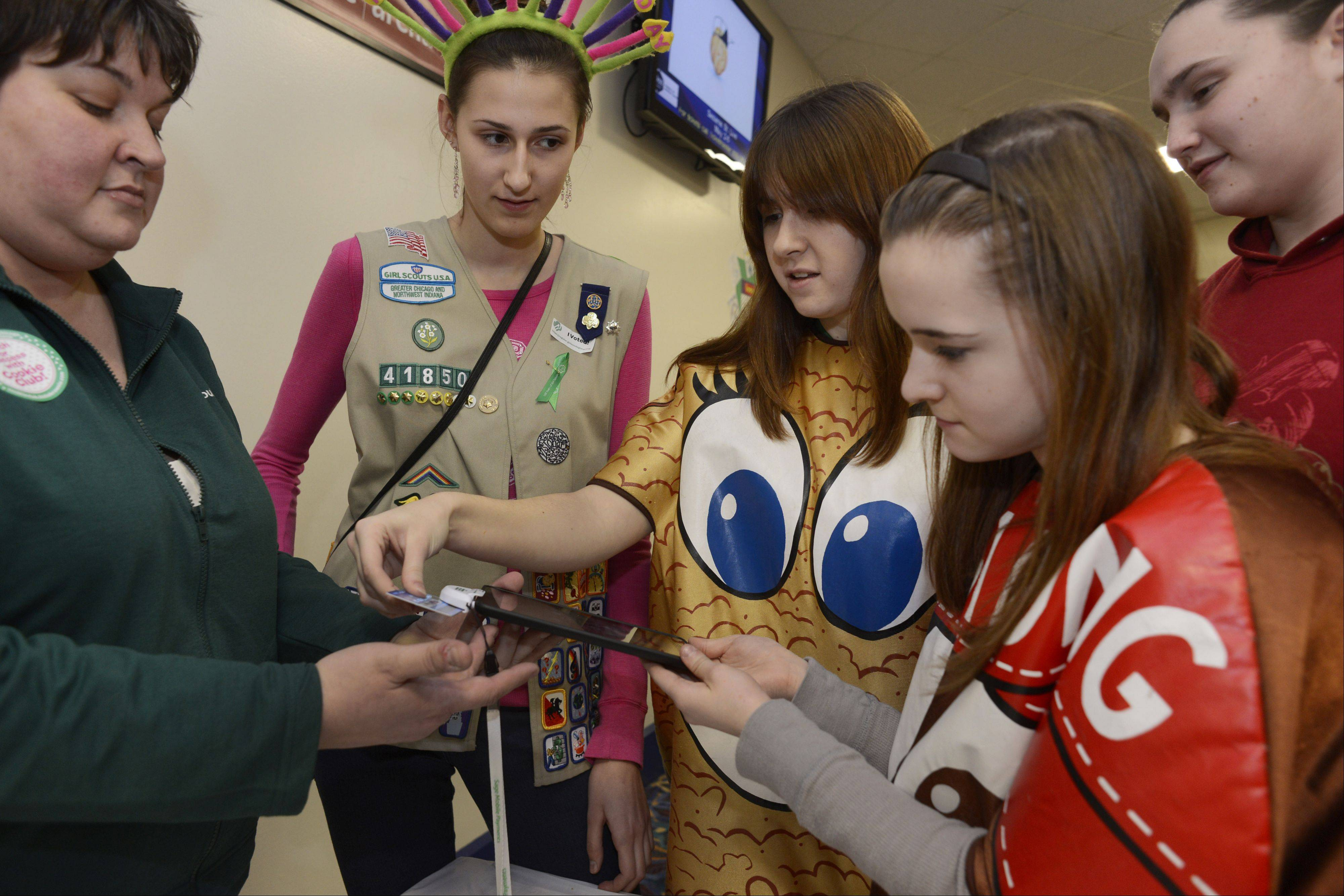 Left to right, Product Program Manager Michelle Kruse shows Tatiana Doroskin, Samantha McKeown, and Madison Korta, all of Schaumburg, and Brianna Randecker of Hoffman Estates how to swipe a credit card as the Girl Scouts of Greater Chicago and Northwest Indiana kicks off its annual Girl Scout Cookie Program Saturday at the Allstate Arena in Rosemont.