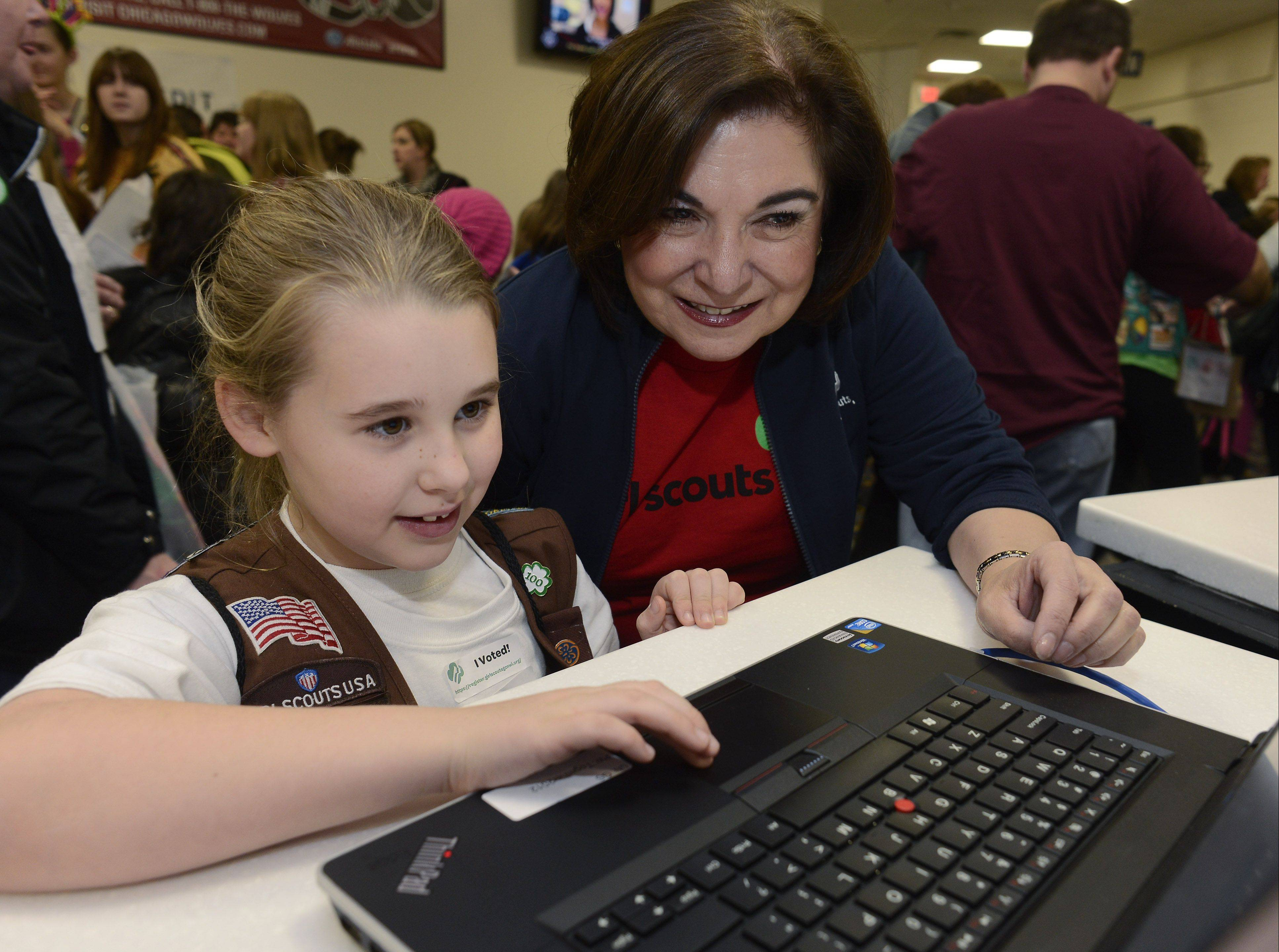Riley Reynolds, 7, of Hoffman Estates, who is a member of Brownie Troop 41857, learns how to view sales information on the computer with the help of Maria Wynne, CEO of the Girl Scouts of Greater Chicago and Northwest Indiana, as the organization kicks off its annual Girl Scout Cookie Program Saturday at the Allstate Arena in Rosemont.