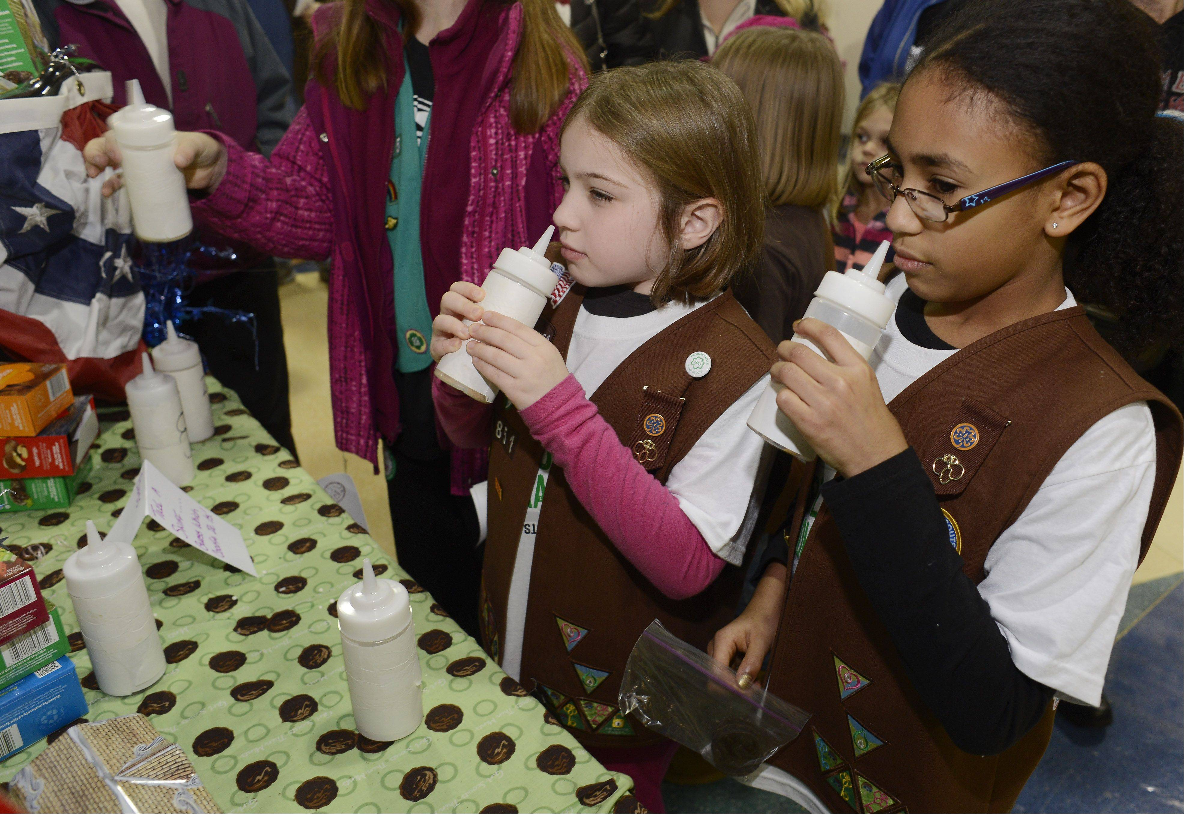 Madalyn Fetterman, 8, left, and Alessandra Carrasquillo, 8, both of Hanover Park and members of Brownie Troop 41857, learn to identify cookies by smell as the Girl Scouts of Greater Chicago and Northwest Indiana kicks off its annual Girl Scout Cookie Program Saturday at the Allstate Arena in Rosemont.
