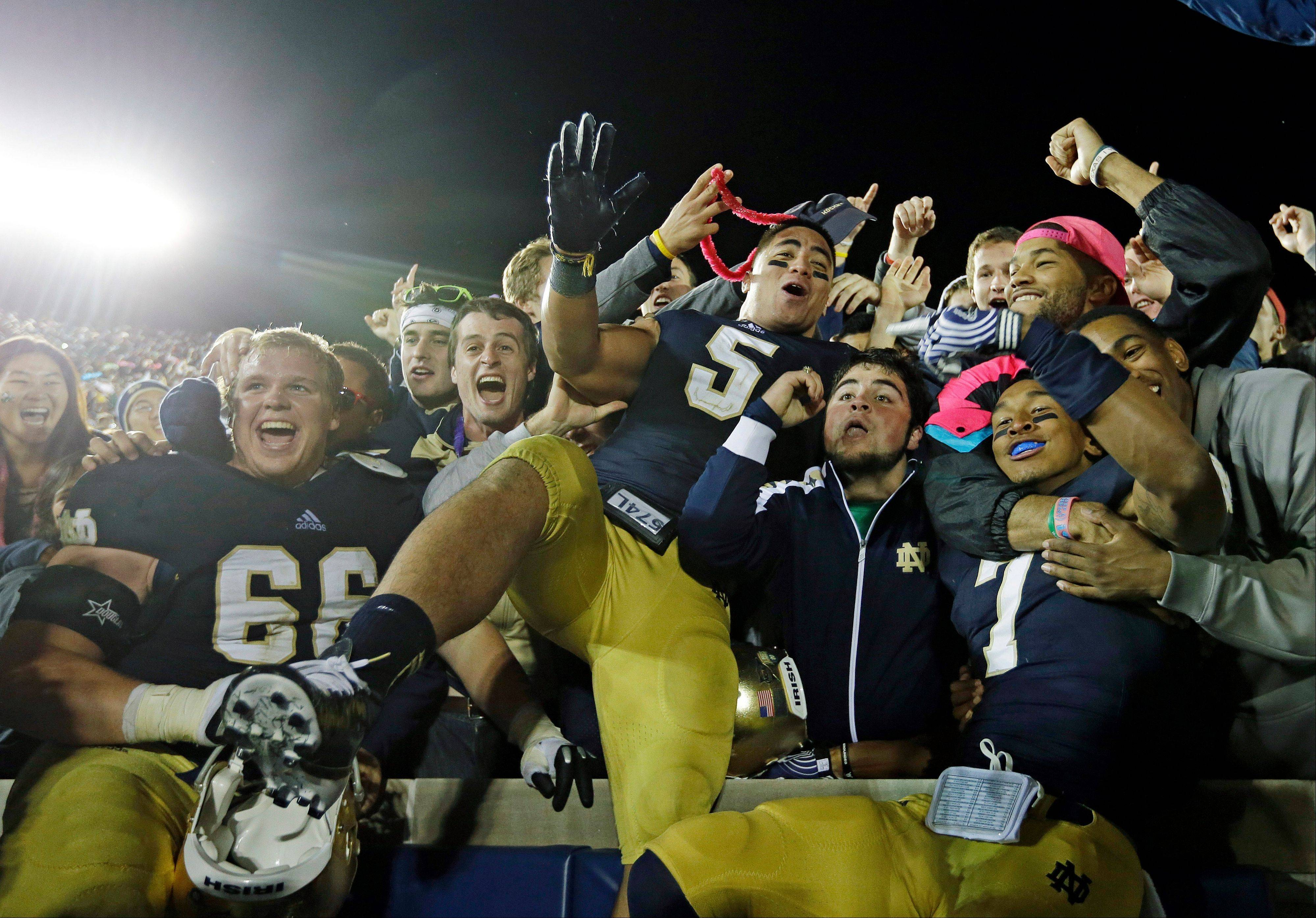 In this Sept. 22, 2012 photo, Notre Dame's Chris Watt (66), Manti Te'o (5) and TJ Jones (7) celebrate with fans after Notre Dame defeated Michigan 13-6 on Sept. 22, 2012, in South Bend, Ind.