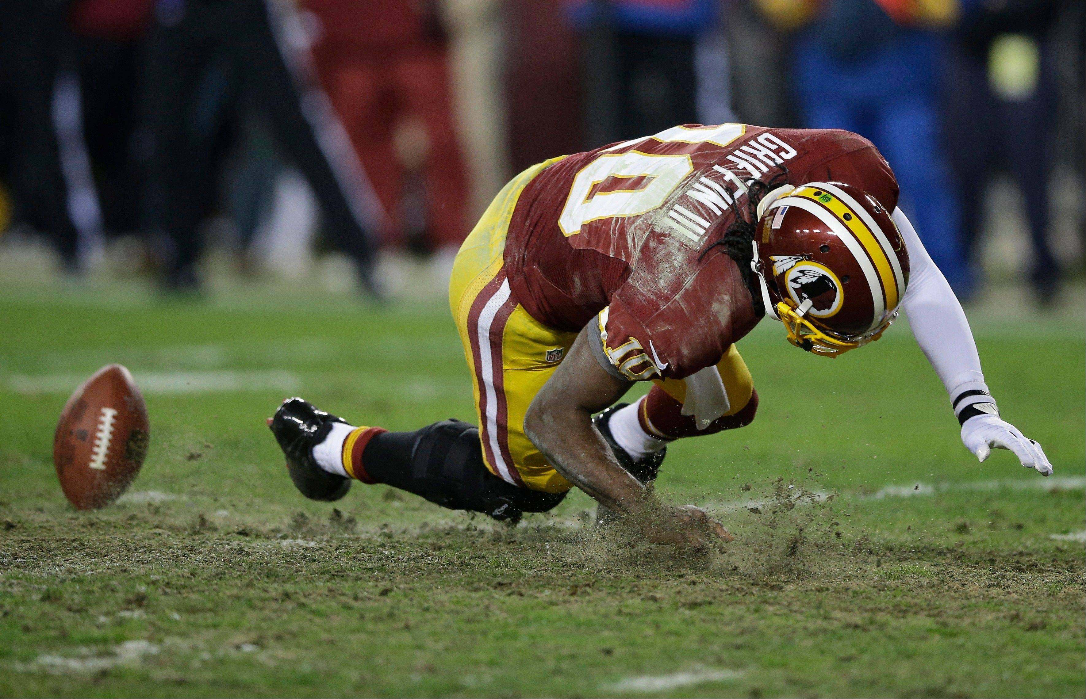 Washington Redskins quarterback Robert Griffin III falls after twisting his knee while reaching for a loose ball during the second half of an NFL wild card playoff football game against the Seattle Seahawks in Landover, Md., Sunday, Jan. 6, 2013.