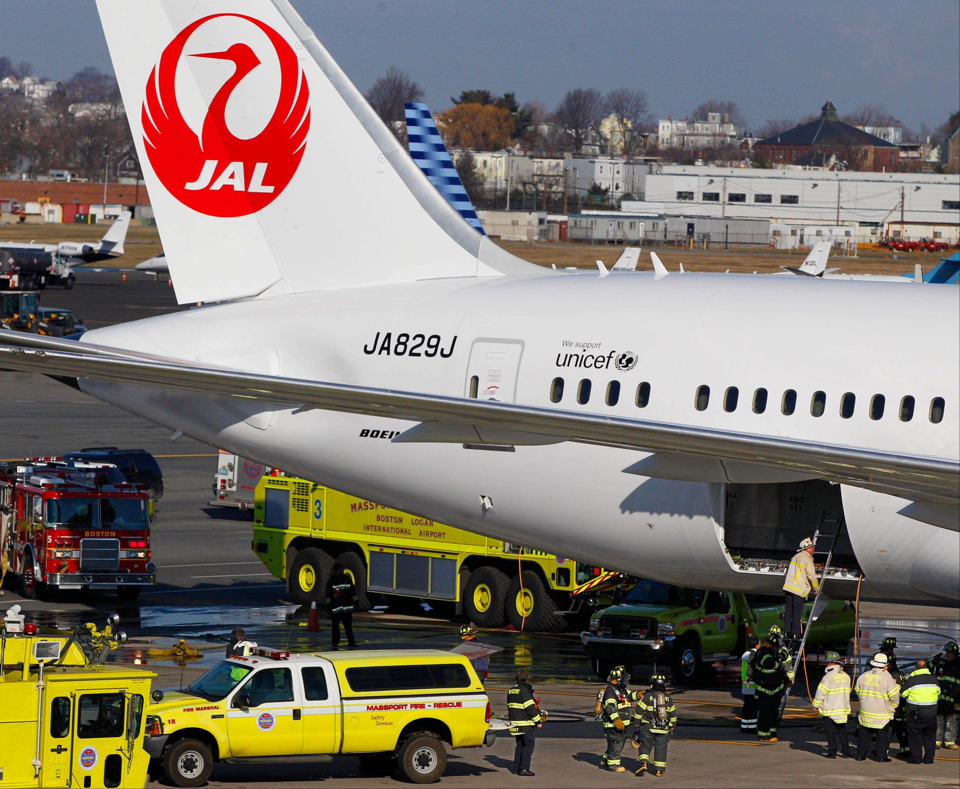 A Japan Airlines Boeing 787 Dreamliner jet aircraft is surrounded by emergency vehicles while parked at a terminal E gate at Logan International Airport in Boston as a fire chief looks into the cargo hold Monday.