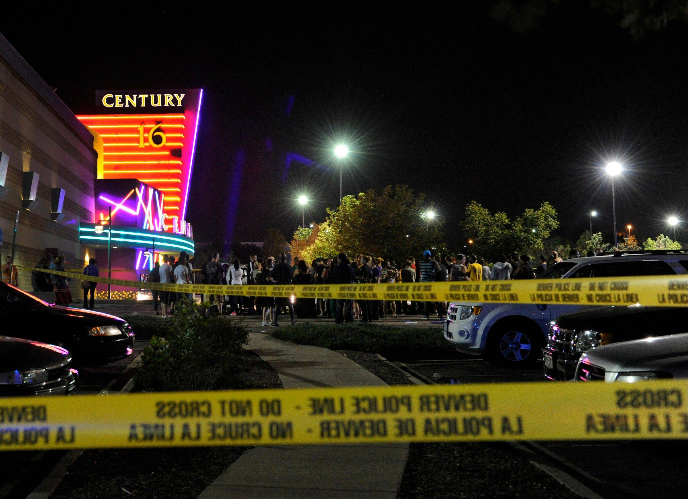 "People gather outside the Century 16 movie theater in Aurora, Colo., following a mass shooting that killed 12 people during a midnight showing of the Batman movie ""The Dark Night Rises"" in July."