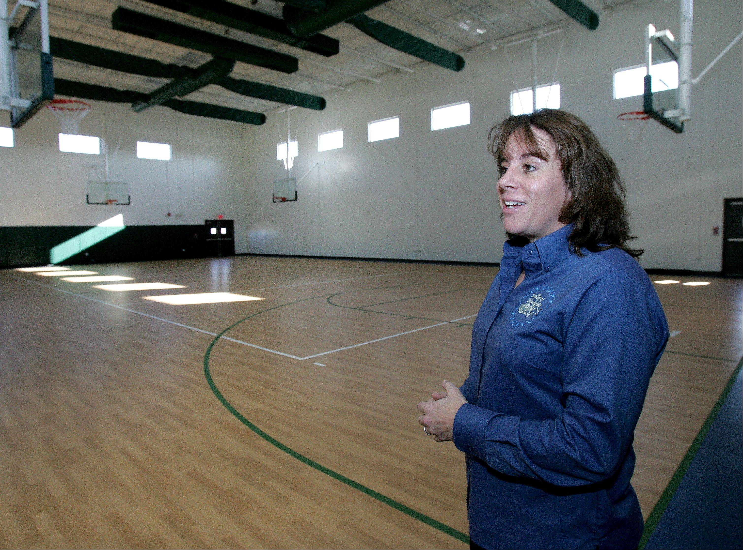Karen Larson, co-founder of the School of Expressive Arts and Learning, shows off the regulation-sized gymnasium at the school's new $5.5 million home in Lombard.