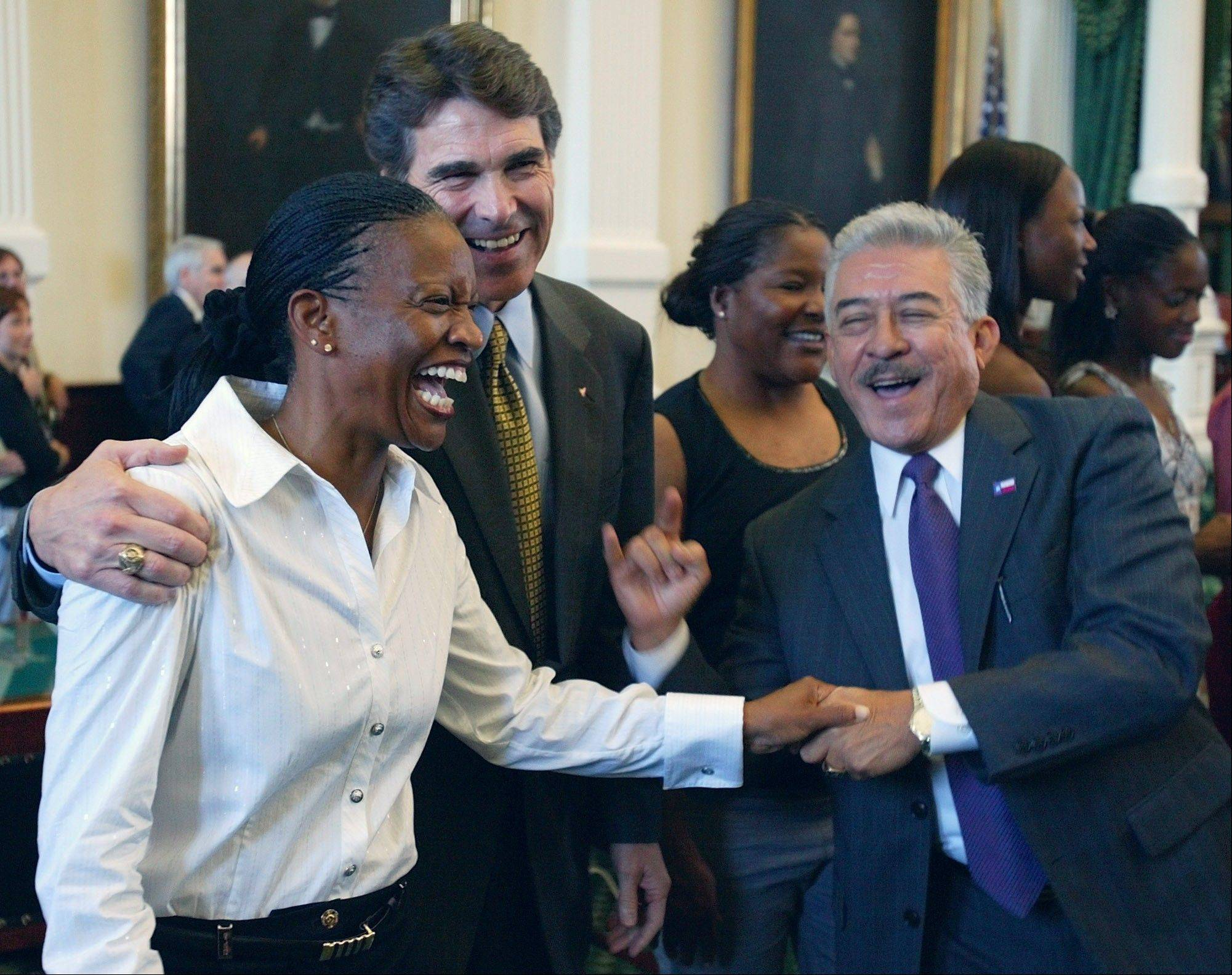 University of Texas women's track coach Bev Kearney, left, shown here being embraced by Texas Gov. Rick Perry during a ceremony to recognize her track team's NCAA championship, has resigned. Kearney admitted to having an intimate relationship with one of her athletes in 2002.
