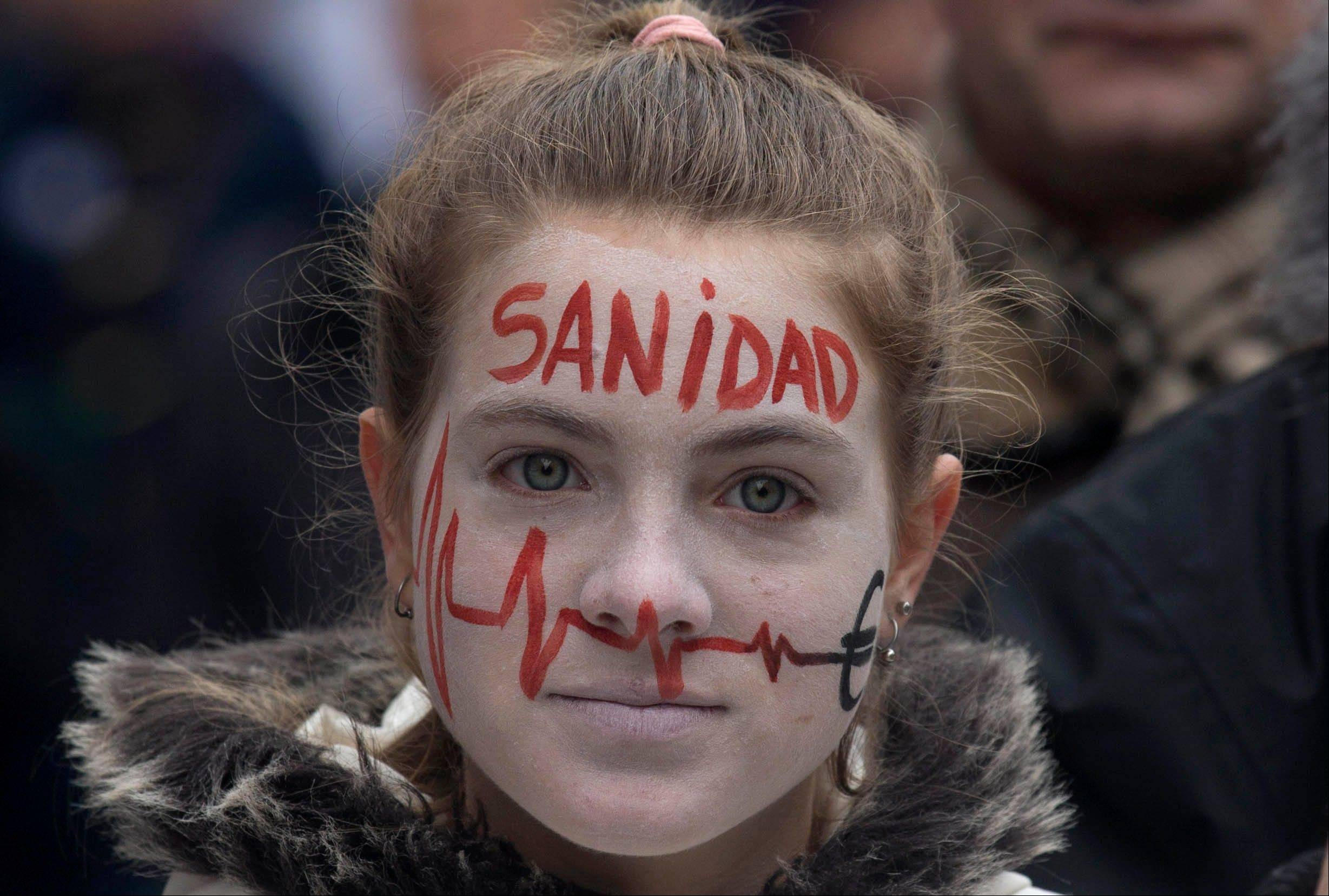 A demonstrator takes part in a National health workers march Monday during the first major demonstration of the year in Madrid. The demonstration was against government-imposed austerity measures and labor reforms in the public health care sector in Madrid. The word painted on her face reads 'Health.'