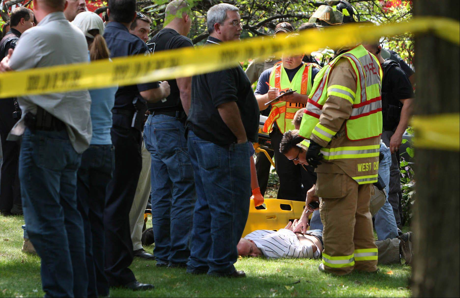 PHOTO BY MIKE ANZALDI Robert Maday, lying on the ground, is surrounded by police and fire officials after crashing his car in West Chicago in September 2009 after a two-day manhunt.