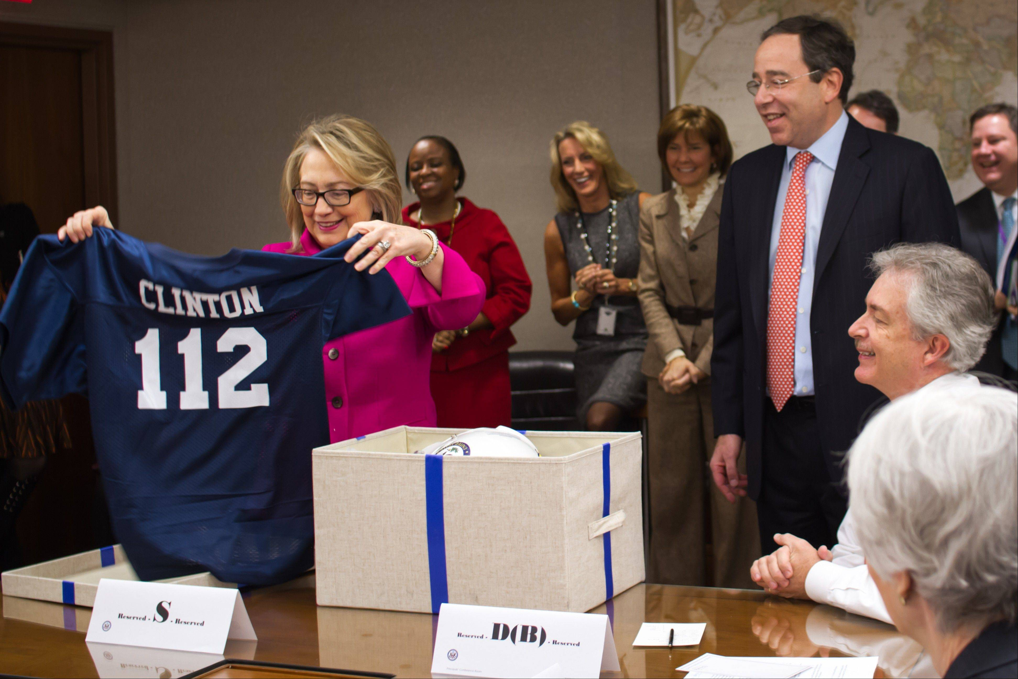 "This handout photo provided by the State Department shows Secretary of State Hillary Rodham Clinton holding up a football jersey, number ""112"" at the State Department in Washington Monday, as she returned to work on Monday after a month-long absence caused first by a stomach virus, then a fall and a concussion and finally a brief hospitalization for a blot clot near her brain. The number 112 refers to the record-breaking number of countries she has visited since becoming secretary of state."