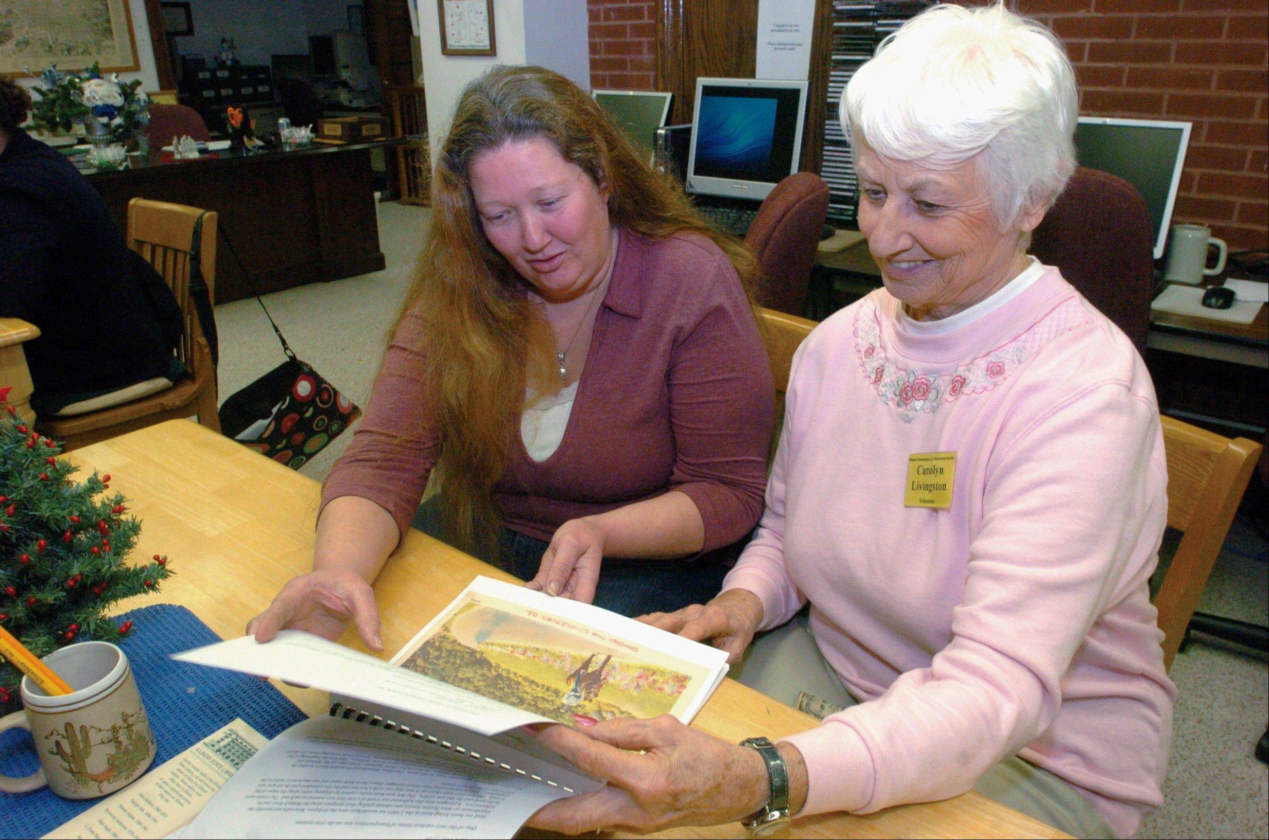 "Michelle Fuller, left, and Carolyn Livingston, volunteers at the Illiana Genealogical and Historical Society In Danville, look through the new post card book ""Plains, Trains and Other Wheels."" This is the third book using old postcards to highlight unique aspects of Vermilion County."