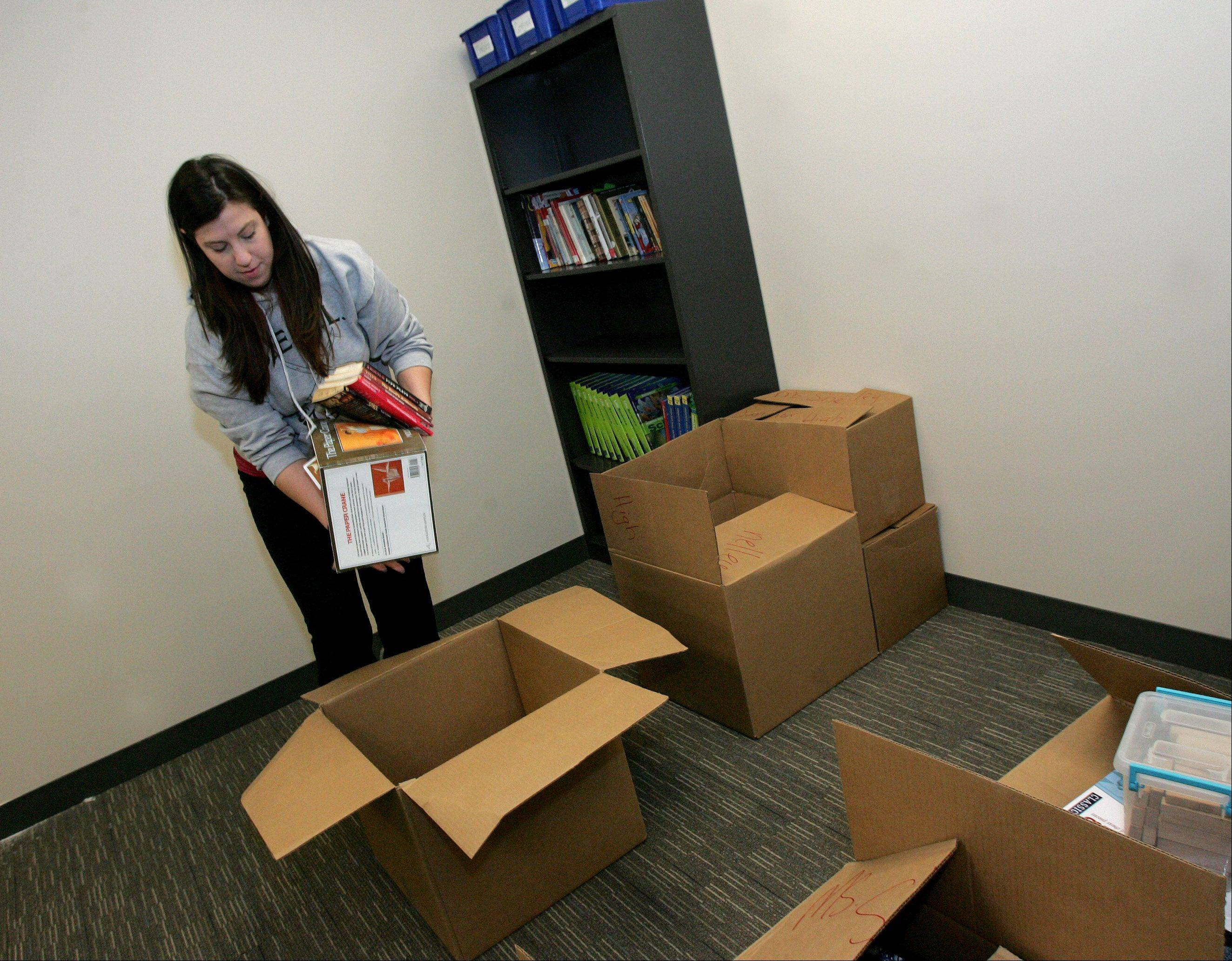 Teacher Shelley Smith unpacks books as she gets her junior high classroom ready at the new location of the School of Expressive Arts and Learning in Lombard. Classes at the $5.5 million facility begin Monday.