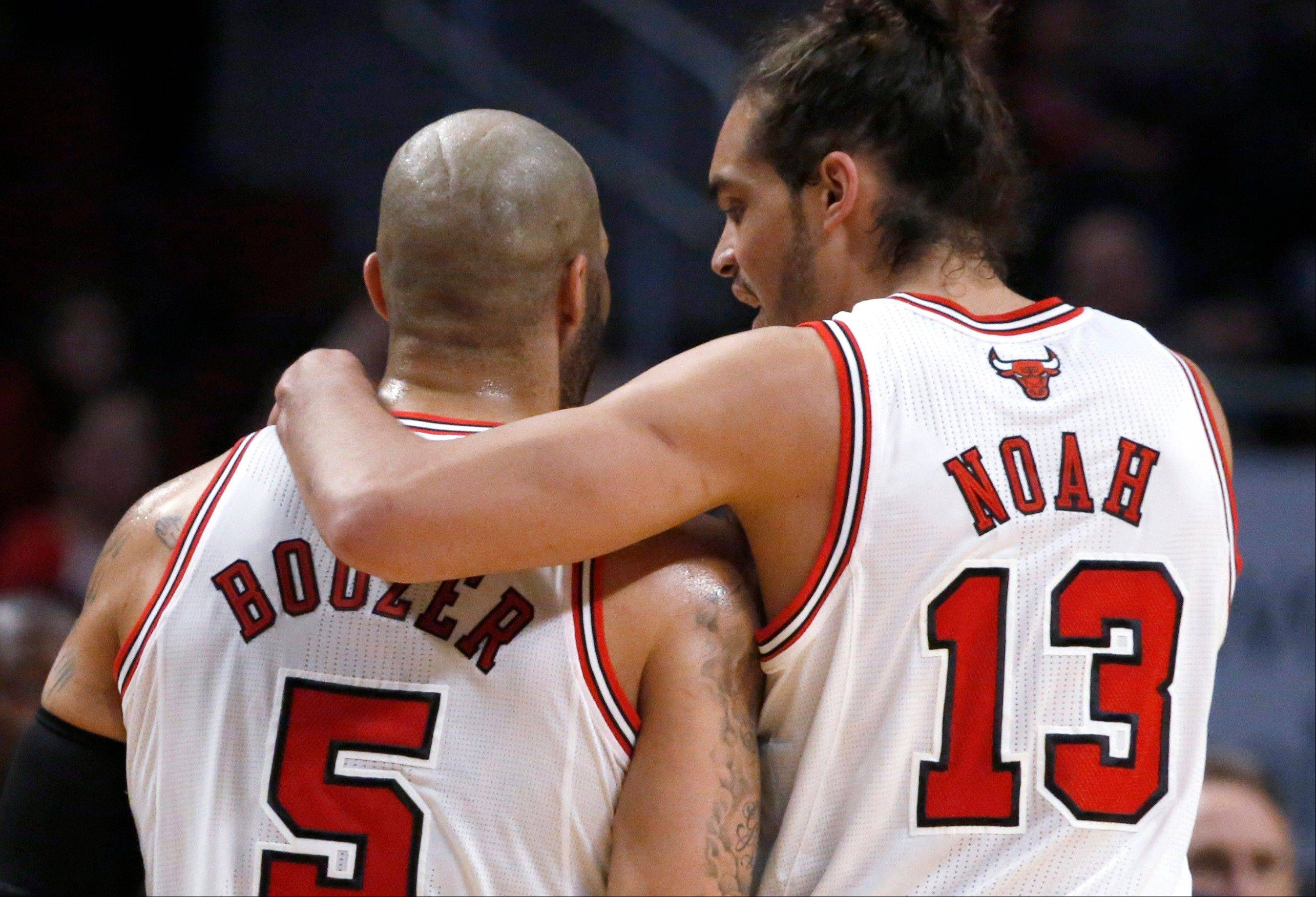 Bulls forward Carlos Boozer and center Joakim Noah talk during a break in the first half of an NBA basketball game against the Cleveland Cavaliers on Monday, Jan. 7, 2013, in Chicago.