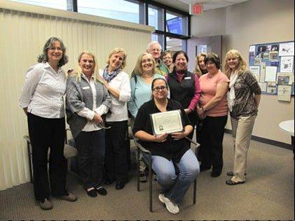 Karen Morelli of Lake in the Hills, seated, displays the Joseph A. Blanco Spirit Award she received from the Special Needs Department at McHenry County College. Pictured with her are tutors and staff members, from left: Charlotte Kremer, Susan Hayes, Janice Jellicoe, Donna Davis, John Healy, Gayle Barkley, Ellen Morton, Peg Wronski, Candy Neumann, and Bev Albright.