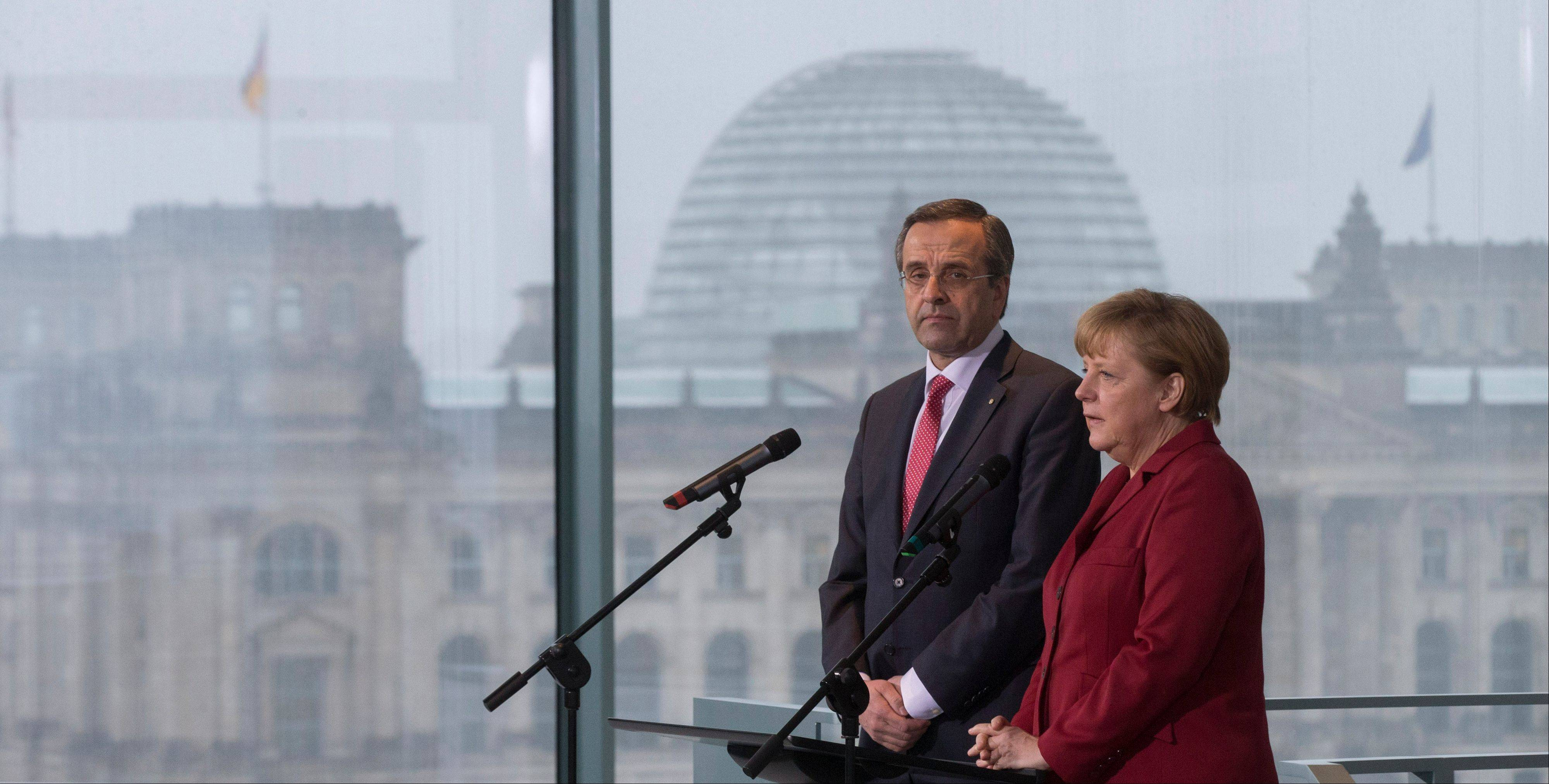 German Chancellor Angela Merkel, right, and the Prime Minister of Greece, Antonis Samaras, give a statement Tuesday prior to a meeting at the chancellery in Berlin.