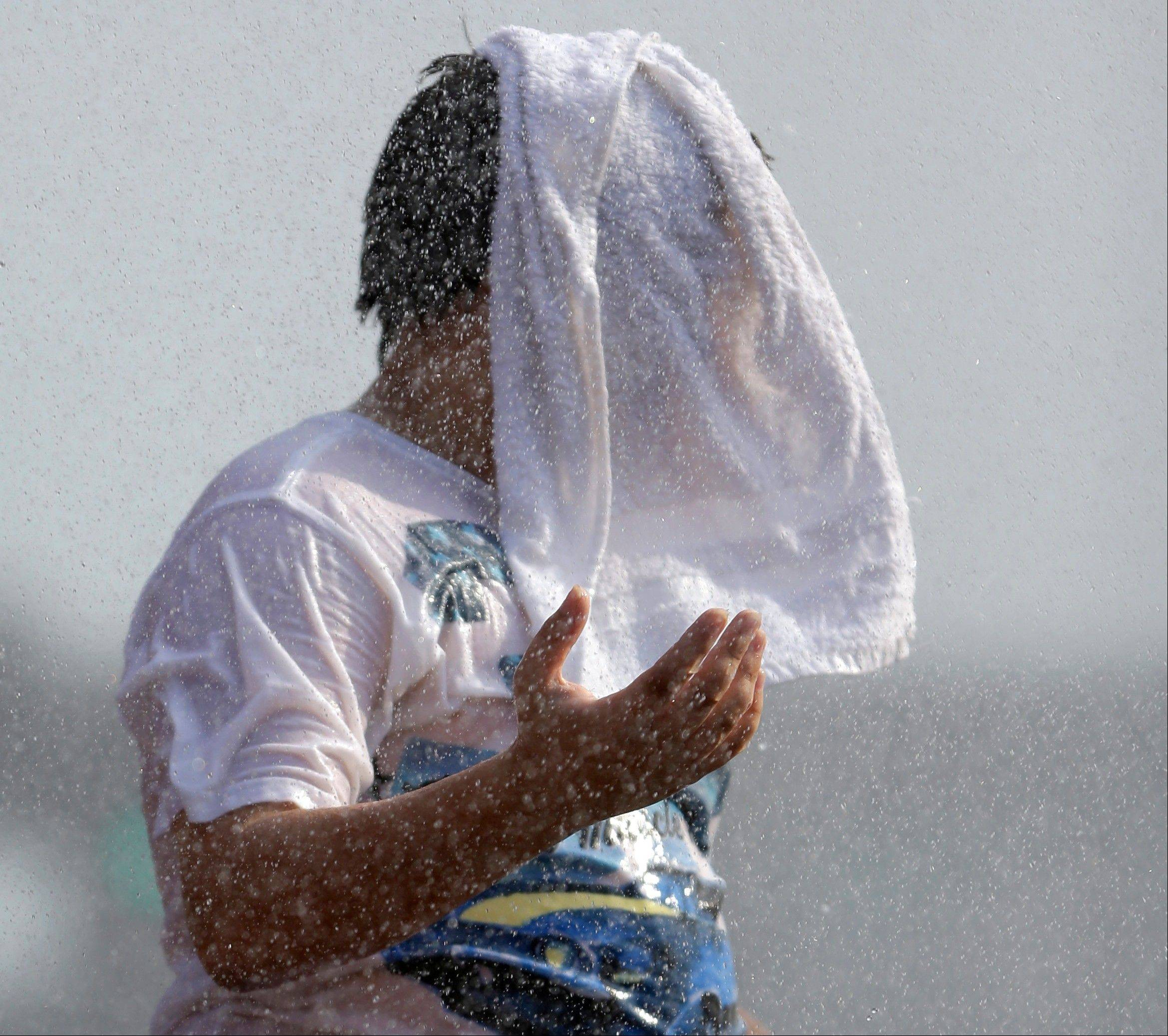 Federal meteorologists say America was deep fried in 2012, becoming the hottest year on record by far. Above, Timmy Benson wears a wet towel on his head as he cools off in a fountain outside Busch Stadium before a St. Louis Cardinals baseball game July 6.
