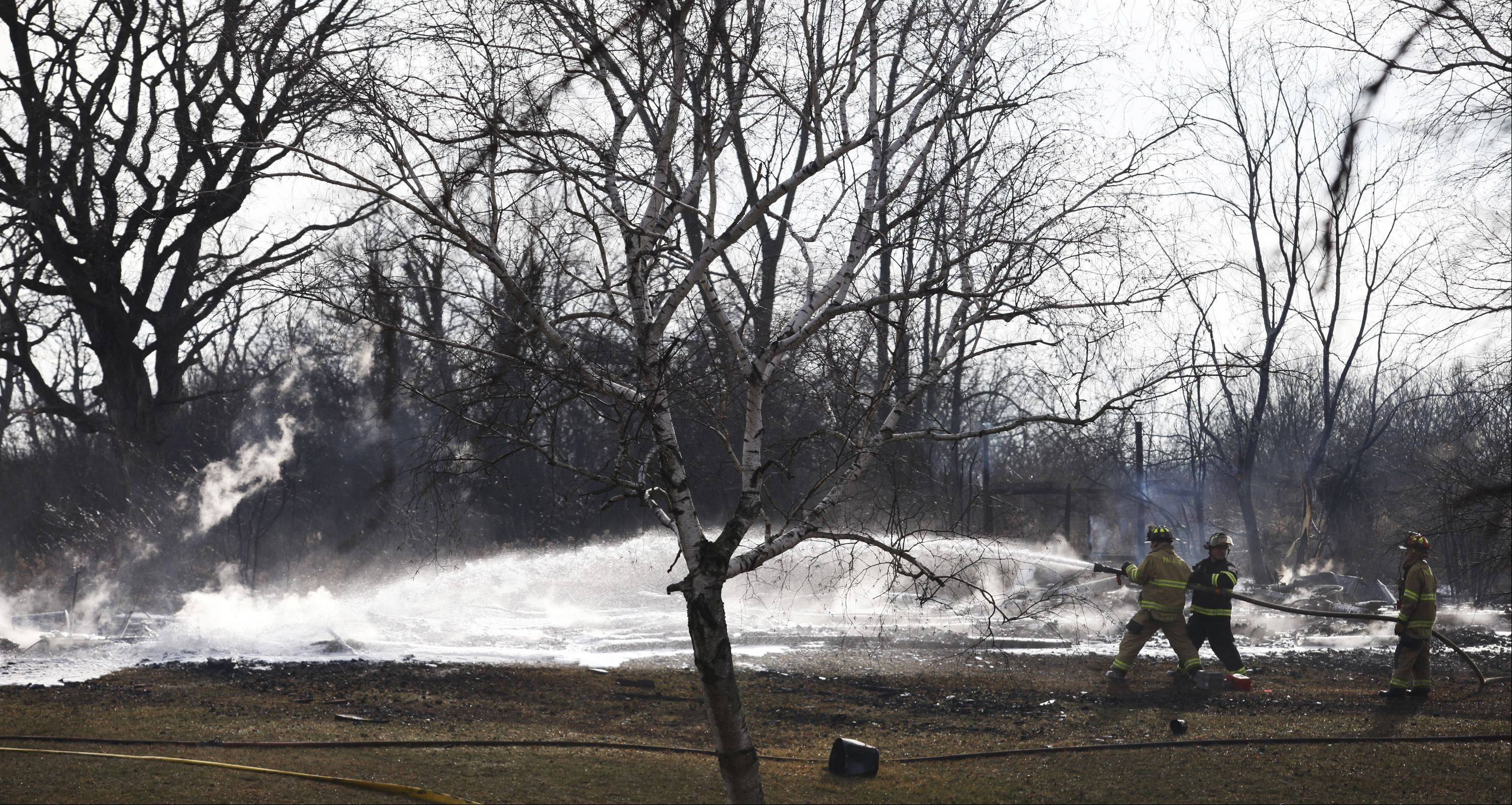 Firefighters pour water on the remnants of a barn fire Tuesday afternoon at a Cook County Forest Preserve District watchman's residence along Penny Road.