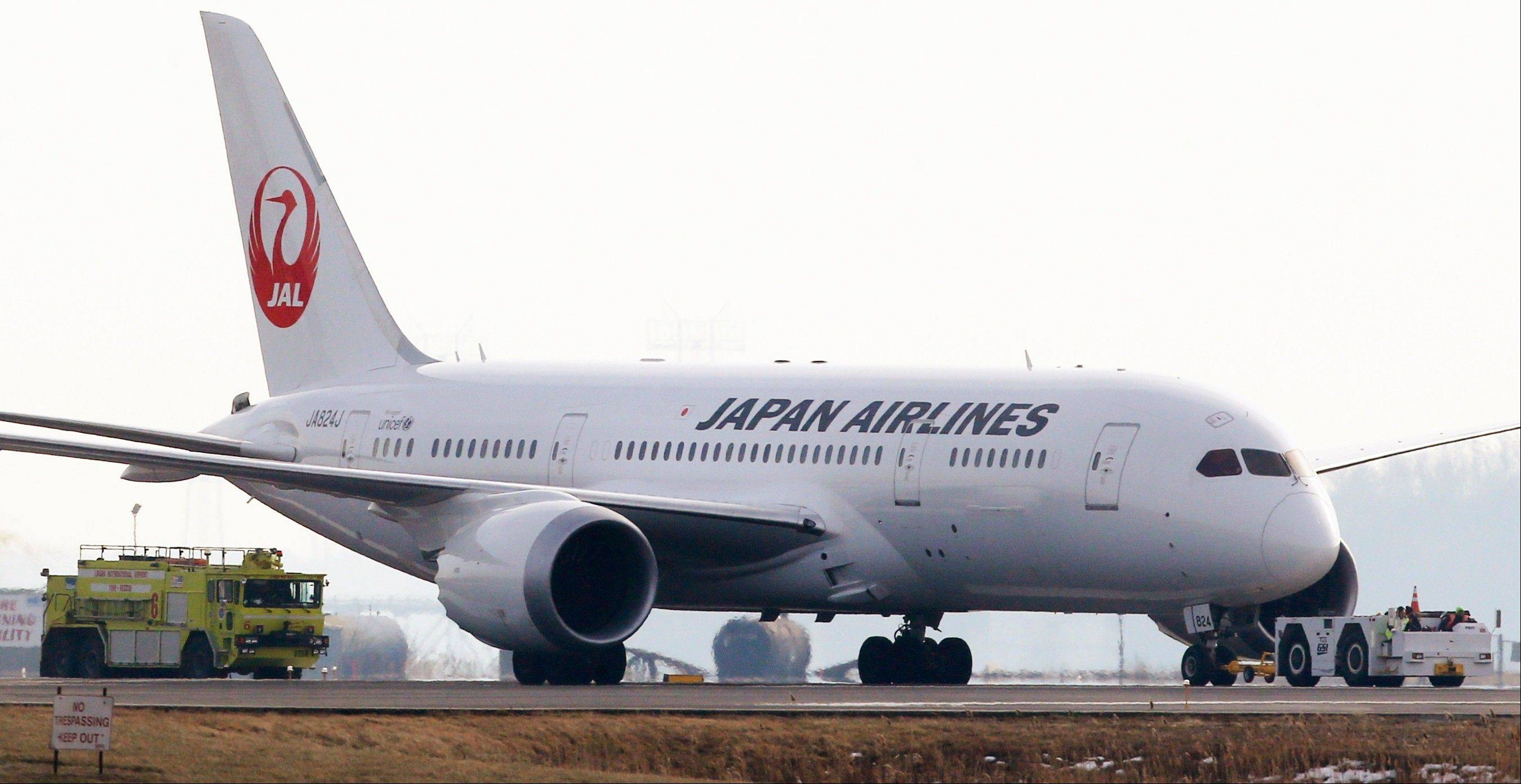A Japan Airlines 787 is escorted by a fire engine as it is towed away from the runways at Logan Airport in Boston Tuesday. Officials say crews have contained a fuel leak from the outbound Japan Airlines flight to Tokyo in the second incident involving the airline at Logan in two days.