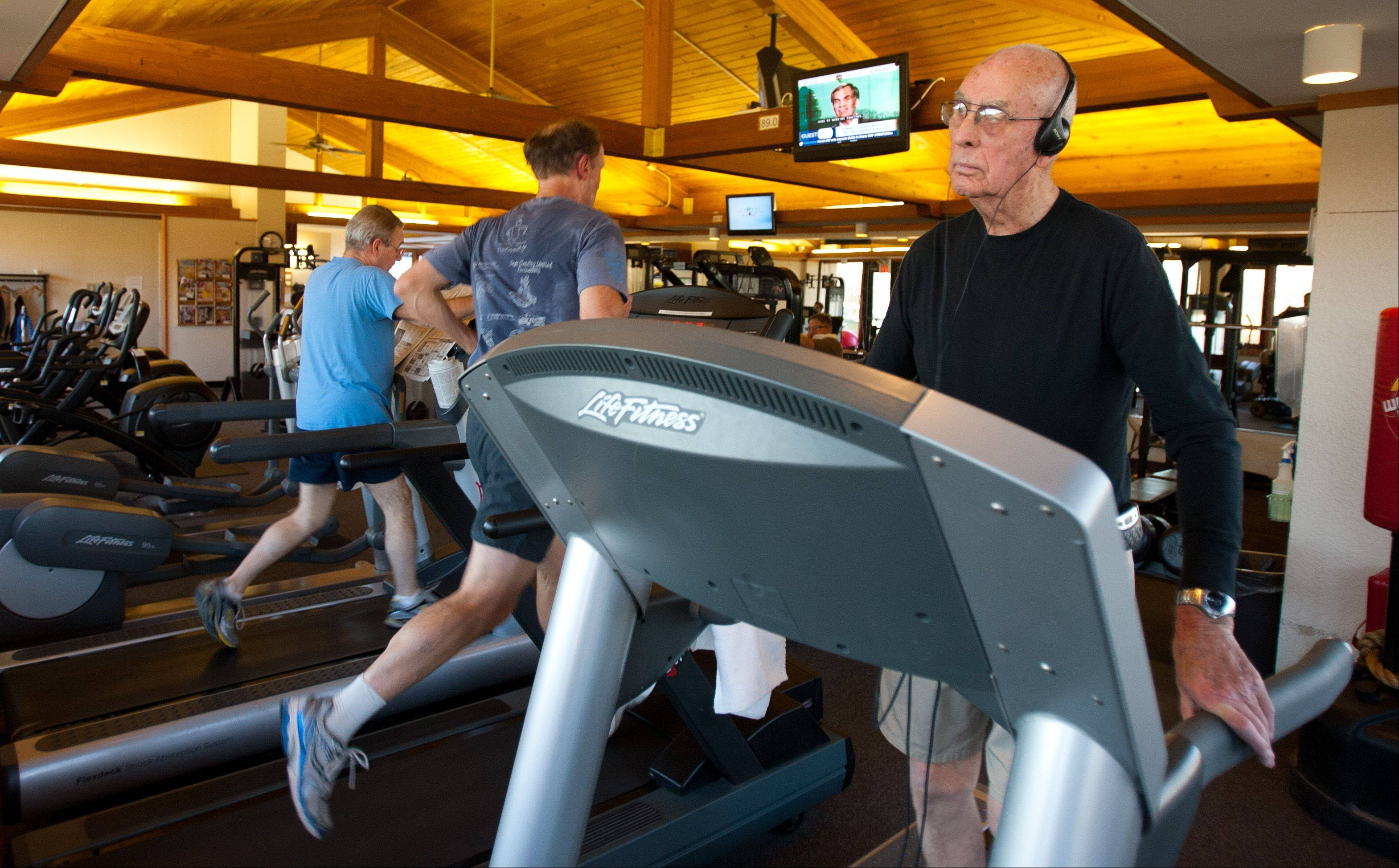 Wearing headphones, 90-year-old Charles Fultz does 35 minutes on the treadmill during his 1½-hour workout.
