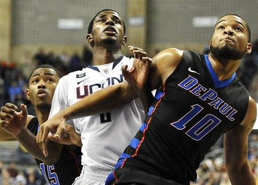 Connecticut's DeAndre Daniels, center looks for a rebound against DePaul's Moses Morgan, left, and DePaul's Derrell Robertson Jr., right, during the first half of an NCAA college basketball game in Storrs, Conn., Tuesday. Co