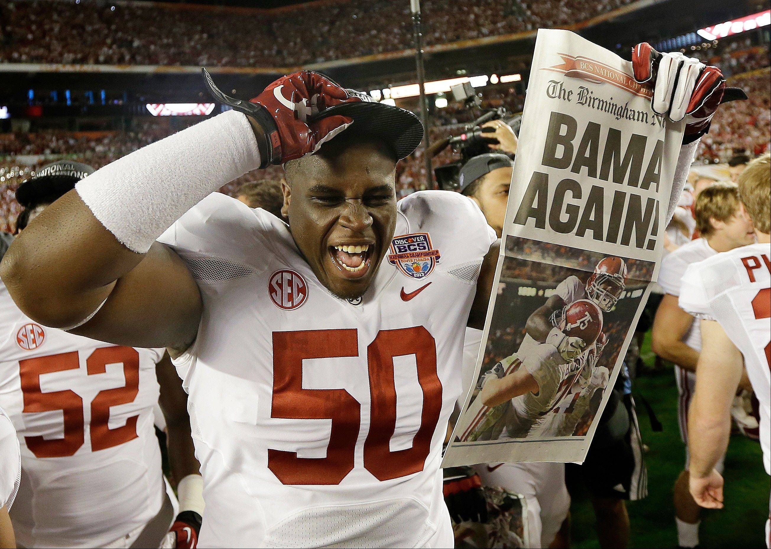 Alabama defensive lineman Alphonse Taylor (50) holds up a newspaper after the BCS National Championship college football game Monday, Jan. 7, 2013, in Miami. Alabama won 42-14.
