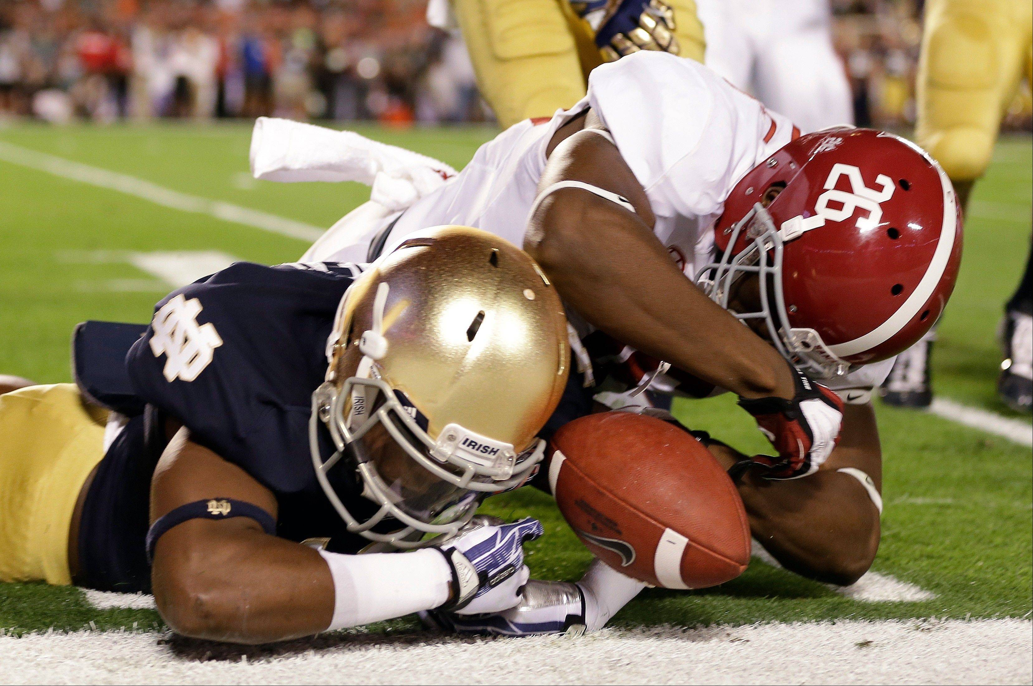 Alabama's Landon Collins (26) and Notre Dame's Davonte' Neal go after a fumbled punt during the first half of the BCS National Championship college football game Monday, Jan. 7, 2013, in Miami. The ball went out of bounds and Notre Dame retained possession.