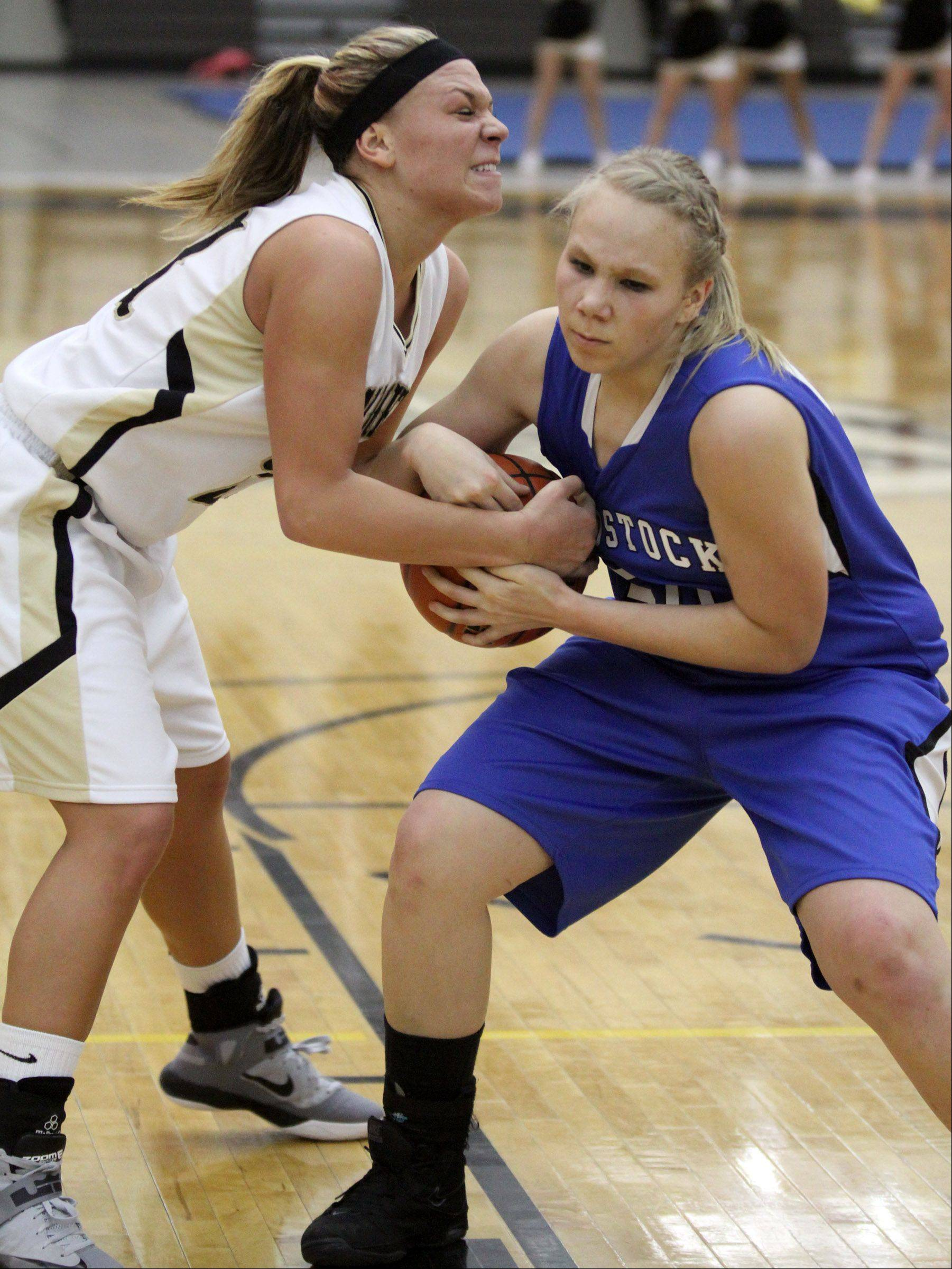 Grayslake North's Shyanne Ludwick fights for the ball with Woodstock's Ari Davis in Grayslake on Friday.