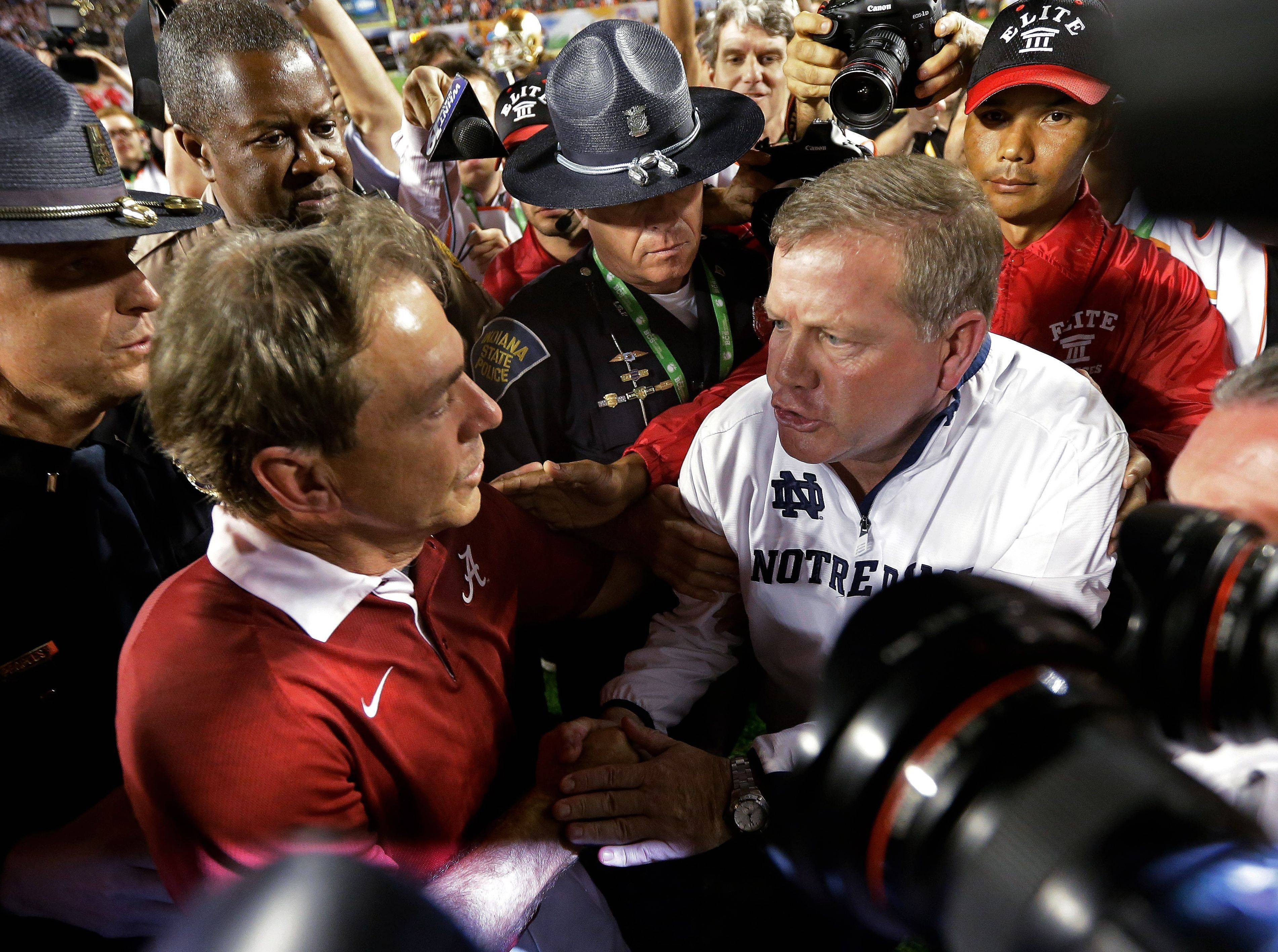 Notre Dame coach Brian Kelly, right, and Alabama coach Nick Saban meet on the field after Monday's BCS championship.