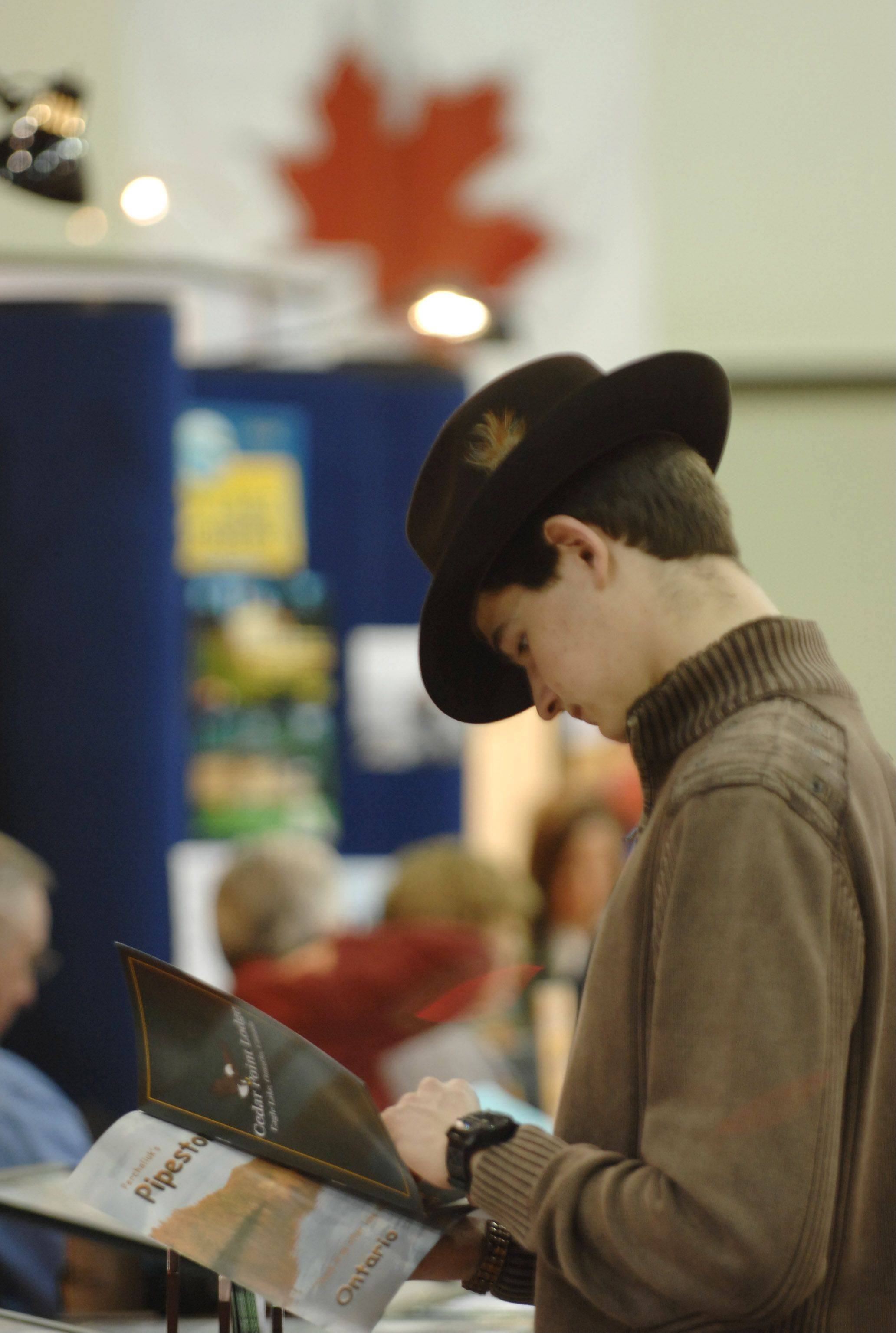 A.J. Englehardt of Lake Bluff flips through a brochure at last year's All-Canada Show at Pheasant Run Resort in St. Charles. The annual show draws those interested in vacation spots, boats, fishing, guns, and all things Canada. A.J. was with his dad, Allan.