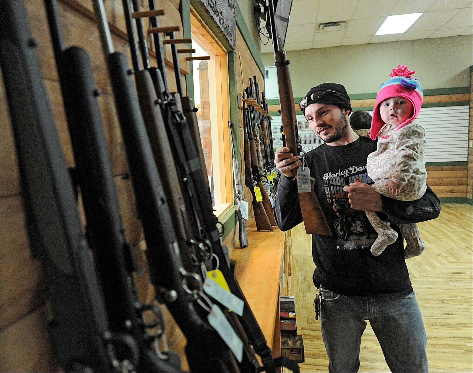 Tyler Hook handles a riffle while holding his 11-month old daughter Emma at Highsmith Guns in Greenfield, Ind. Hook, a U.S. Army veteran who just recently served in Southern Afghanistan and Kandahar, is a gun enthusiast. Highsmith Guns is seeing a rush on semi-automatic riffles with the AR-15 and AK-47 as the most popular.