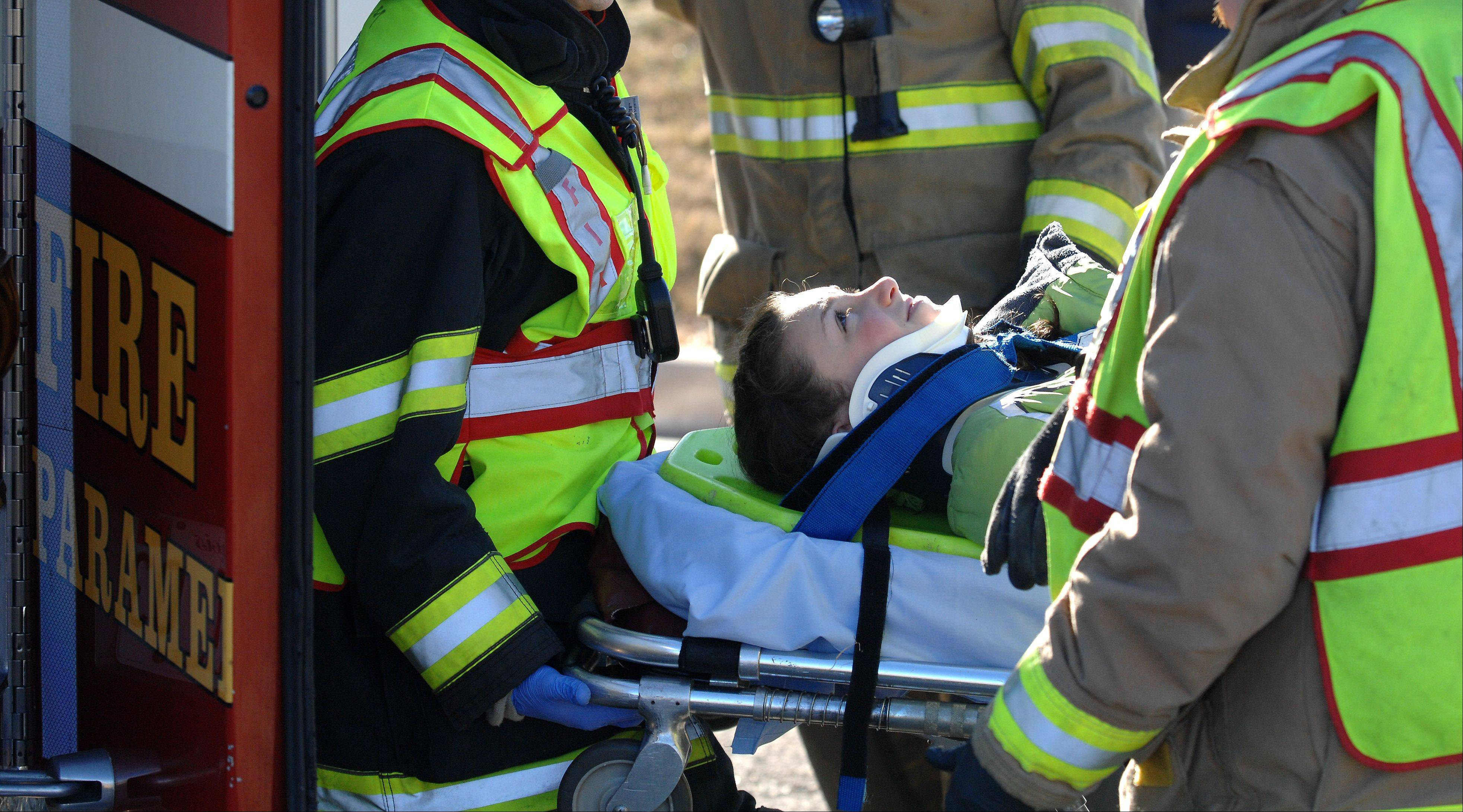 Rotolo Middle School eighth-grader Rebecca Cox plays an injured student Wednesday during an emergency training exercise to simulate the collision of a vehicle with a school bus carrying students.