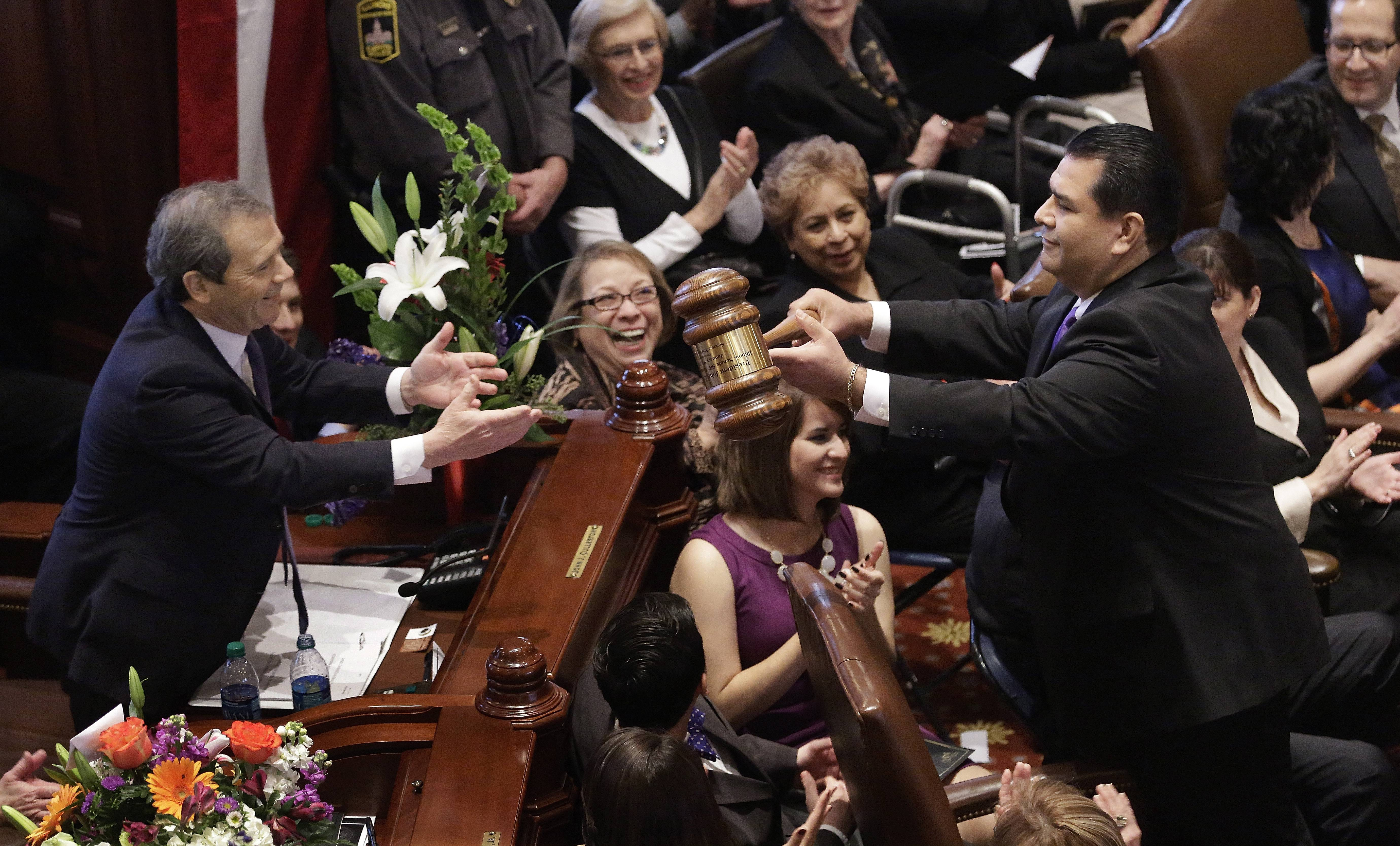 Illinois Senate President John Cullerton, a Chicago Democrat, left, is handed an oversized gavel by Illinois Sen. Martin Sandoval, a Cicero Democrat, Wednesday during swearing ceremonies on the Senate floor at the Illinois State Capitol.