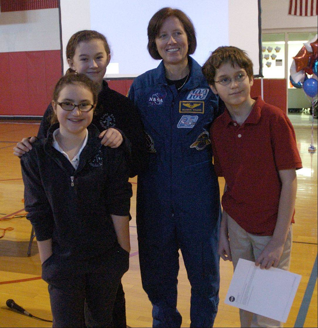 NASA astronaut Shannon Walker poses with St. Anne School students, from left, Grace Lambertsen, Sophia Coombs and Brandon Sadowski.