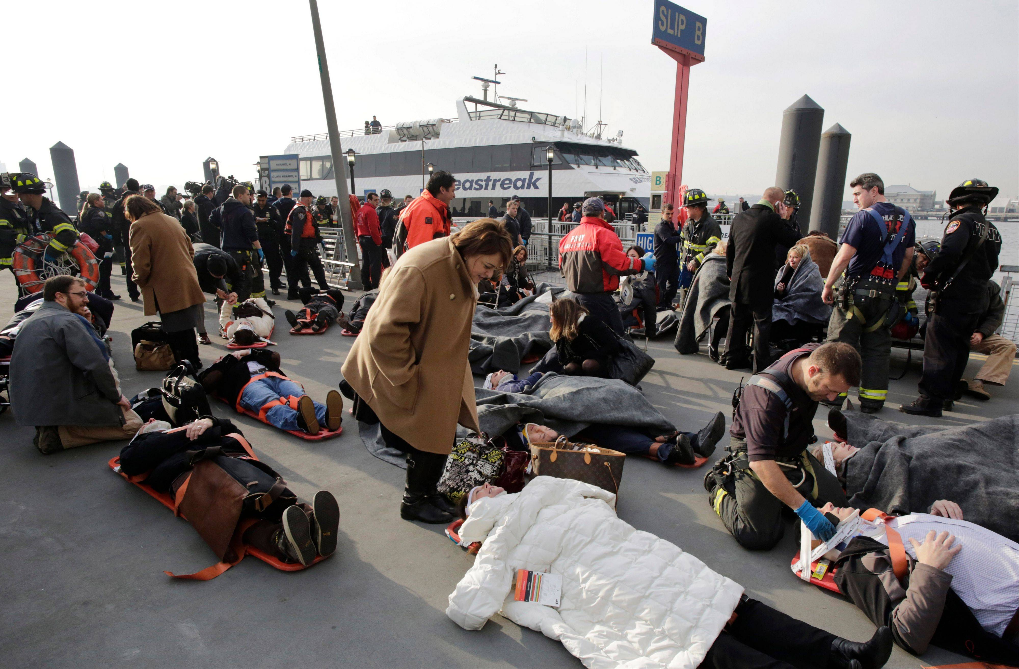 Victims of the Seastreak Wall Street ferry accident are aided by rescue personnel, Wednesday, Jan. 9, 2013 in New York. The ferry, rear, from New Jersey made a hard landing at the dock as it pulled up to lower Manhattan during Wednesday morning rush hour, injuring as many as 50 people, at least one critically, officials said.