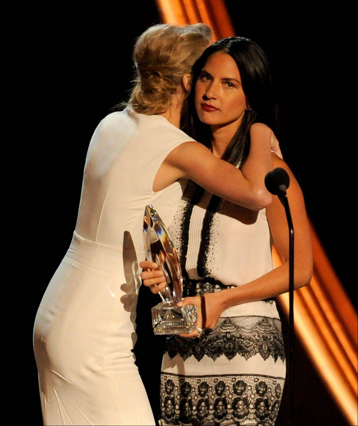 Taylor Swift, left, hugs presenter Olivia Munn before accepting the award for favorite country artist at the People's Choice Awards at the Nokia Theatre on Wednesday Jan. 9, 2013, in Los Angeles.