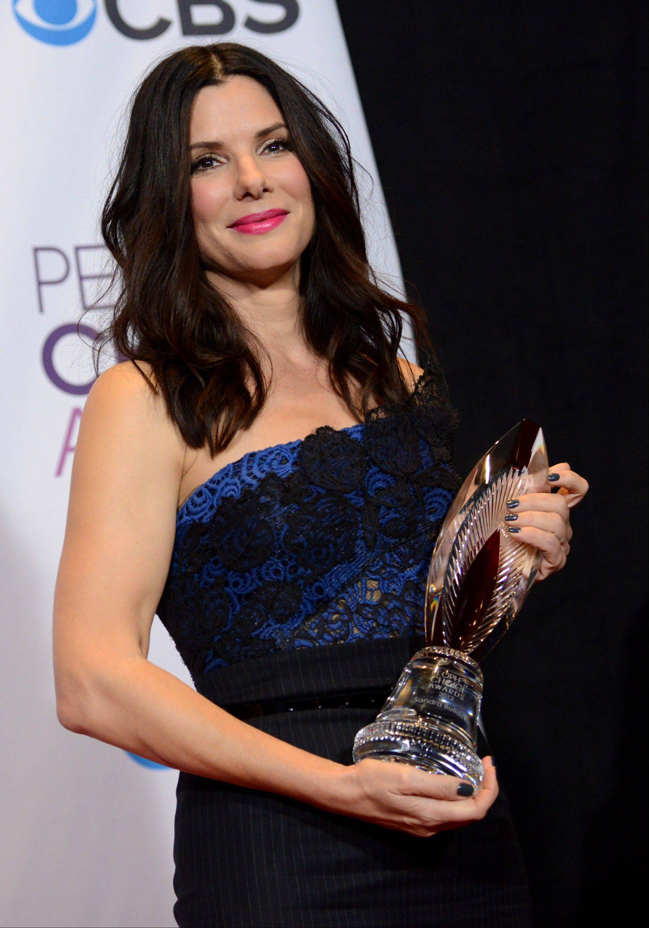 Sandra Bullock poses backstage with the award for favorite humanitarian at the People's Choice Awards at the Nokia Theatre on Wednesday Jan. 9, 2013, in Los Angeles.