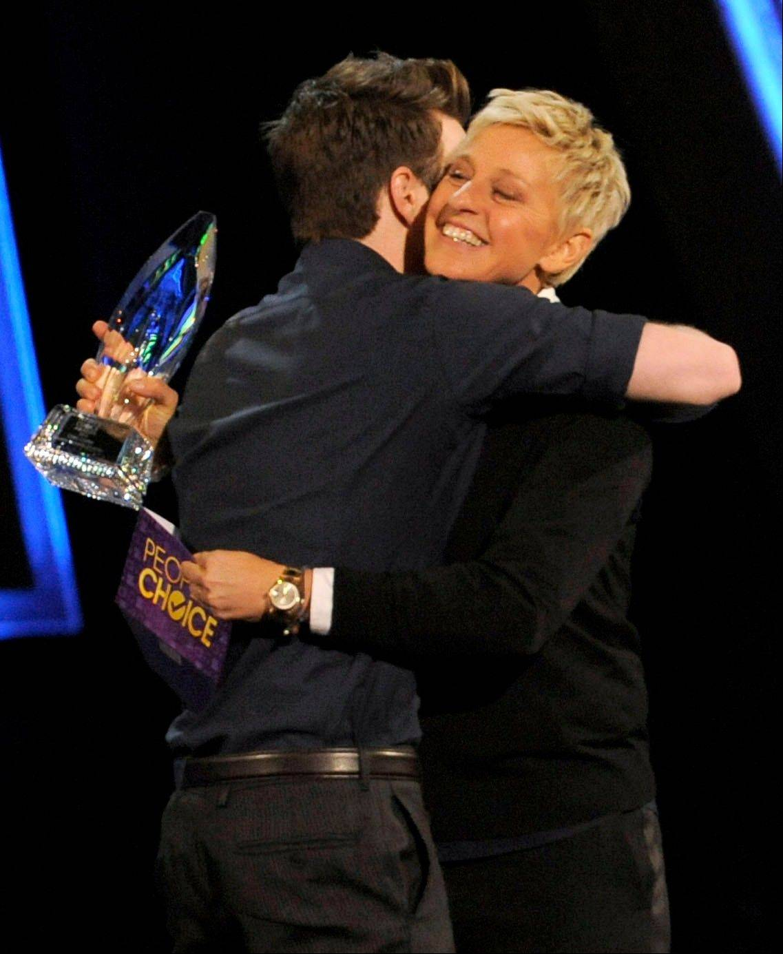 Chris Colfer, left, accepts the award for favorite comedic TV actor from presenter Ellen Degeneres at the People�s Choice Awards at the Nokia Theatre on Wednesday Jan. 9, 2013, in Los Angeles.