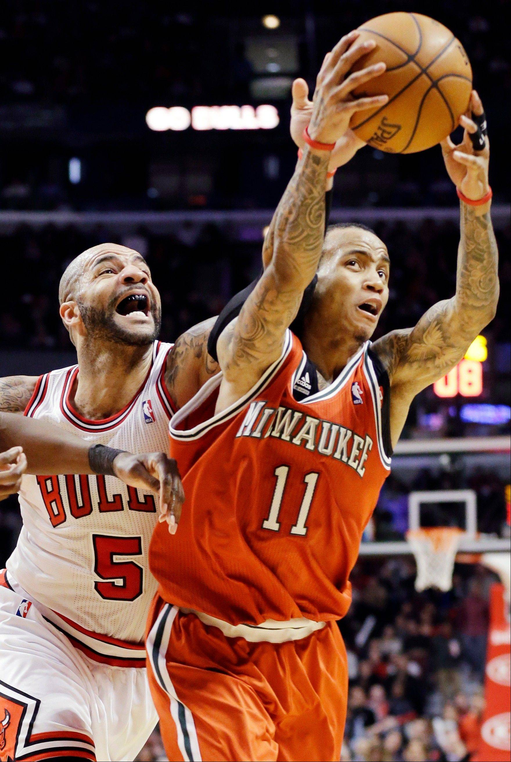 The Bulls' Carlos Boozer battles the Bucks' Monta Ellis for a loose ball.