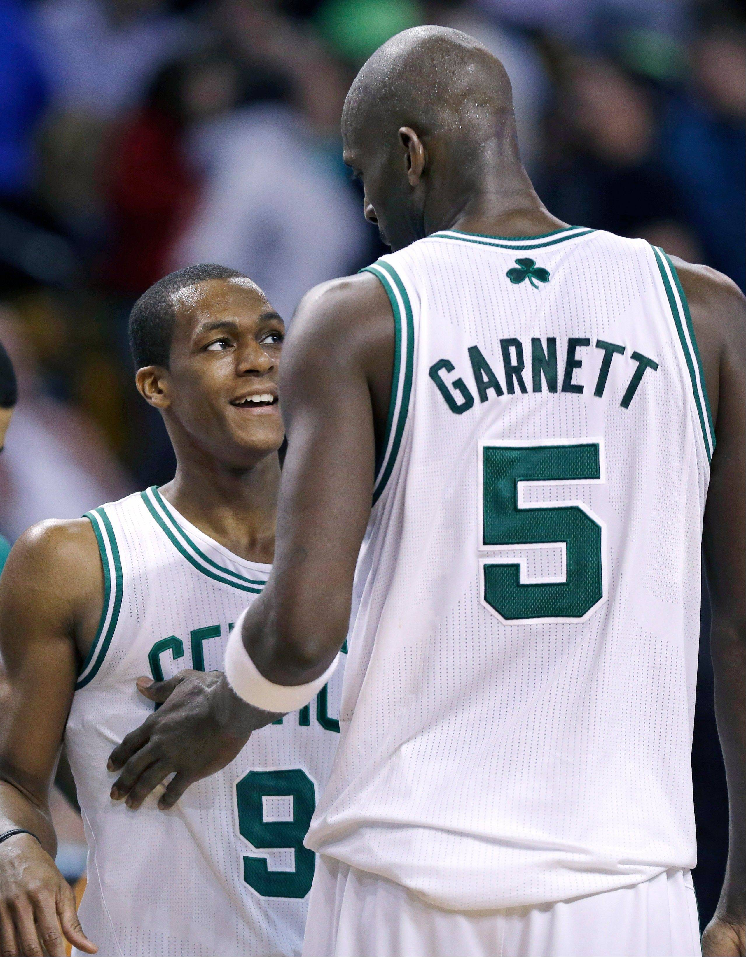 Boston Celtics forward Kevin Garnett (5) pats guard Rajon Rondo (9) on the chest near the end of an NBA basketball game Wednesday against the Phoenix Suns in Boston. The Celtics won 87-79.
