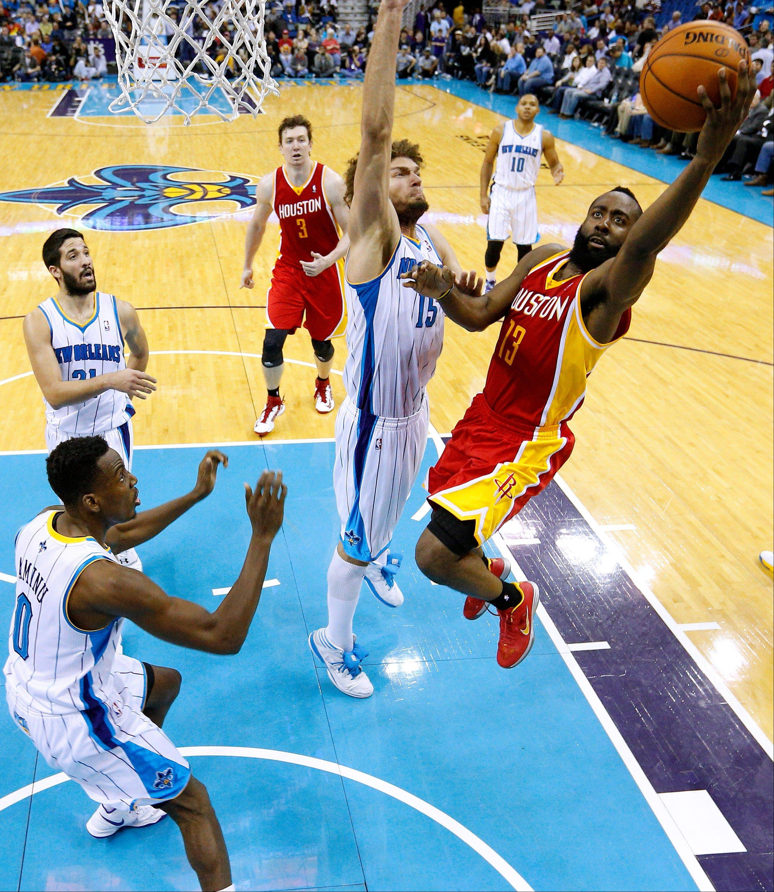 Houston Rockets shooting guard James Harden (13) goes to the basket against New Orleans Hornets center Robin Lopez (15) during the second half of an NBA basketball game Wednesday in New Orleans. The Hornets won 88-79.
