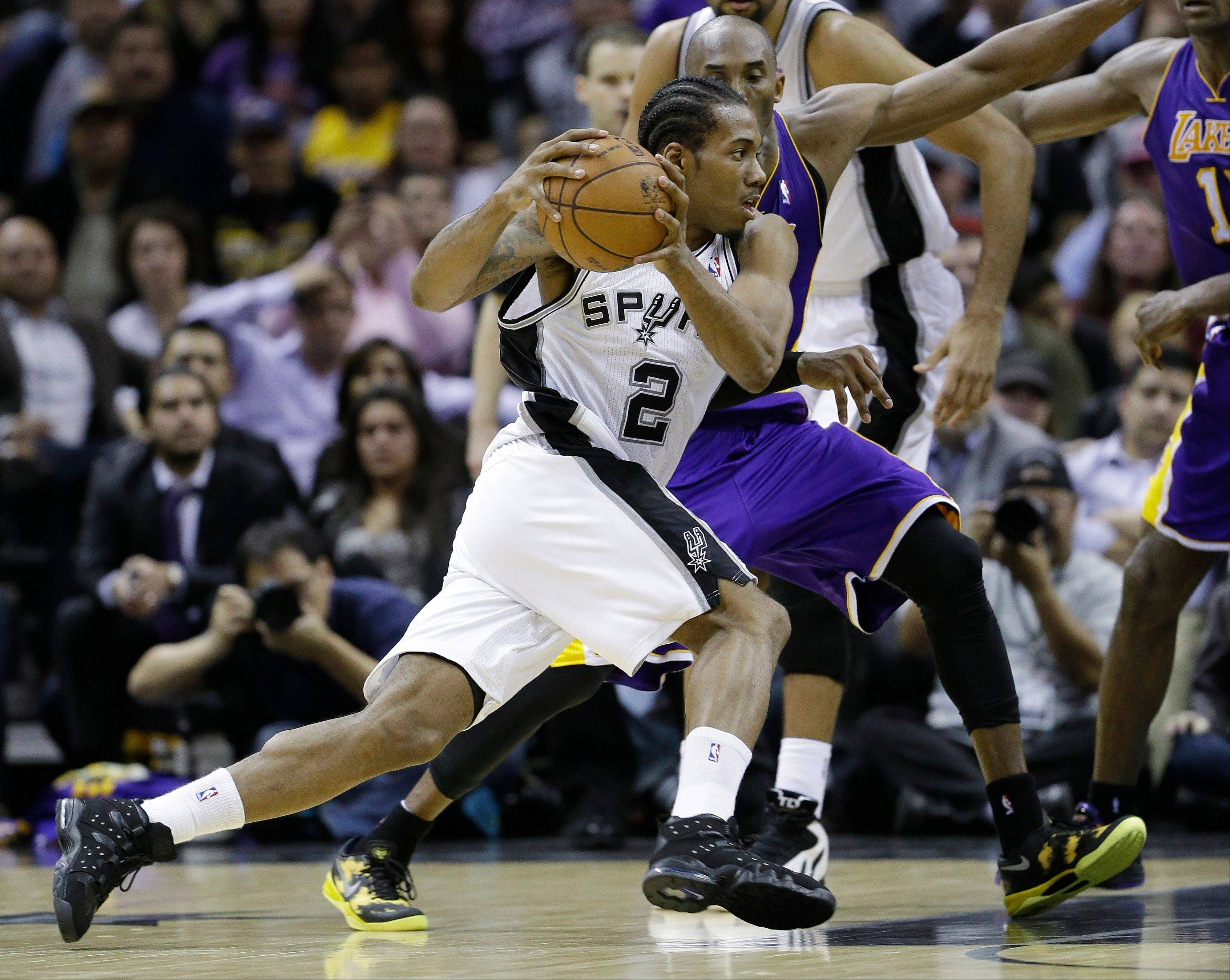 San Antonio Spurs' Kawhi Leonard (2) reaces around Los Angeles Lakers' Kobe Bryant, right, during the fourth quarter of an NBA basketball game on Wednesday in San Antonio. San Antonio won 108-105.