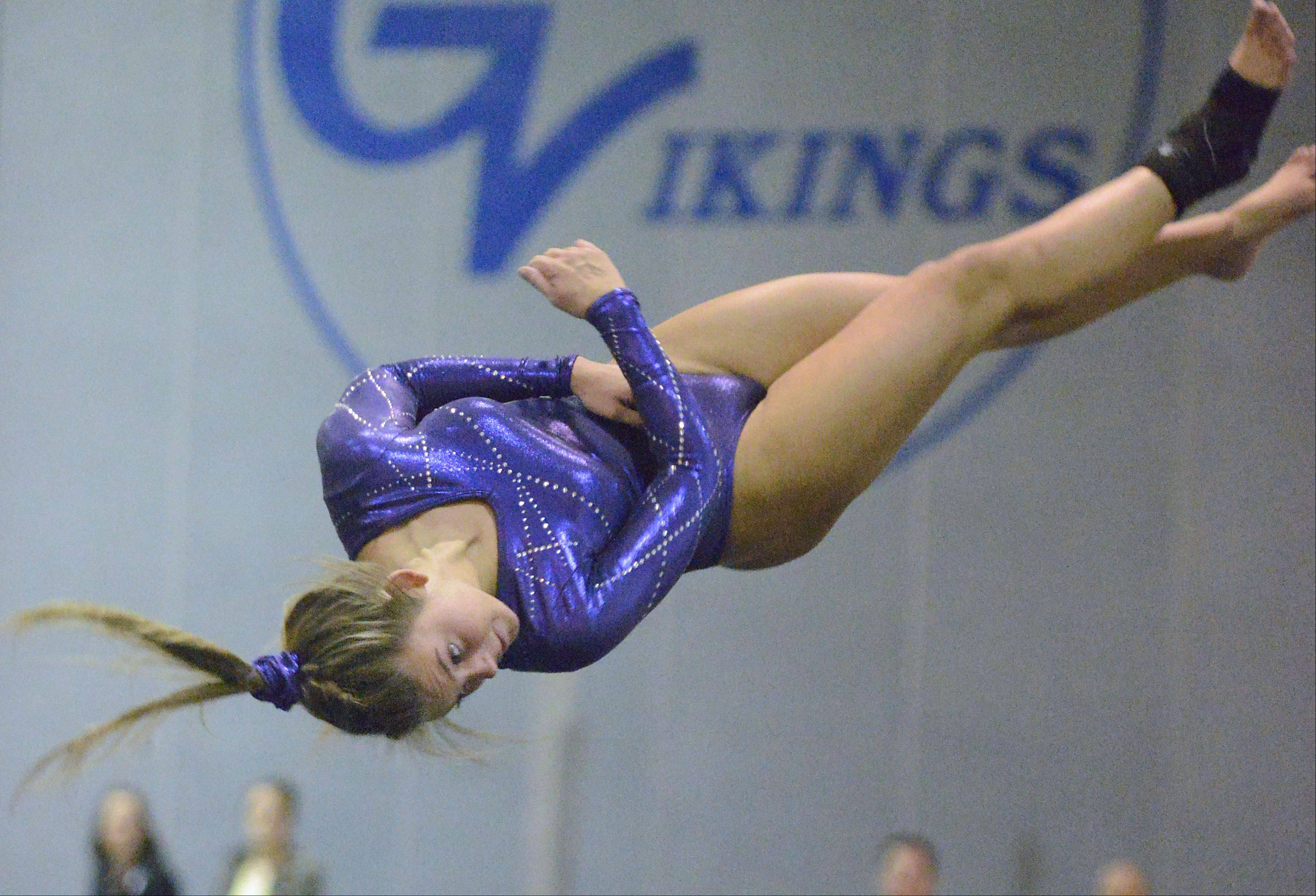 St. Charles' Jesi Ortiz twists in mid air while performing her floor exercise on Wednesday, January 9.