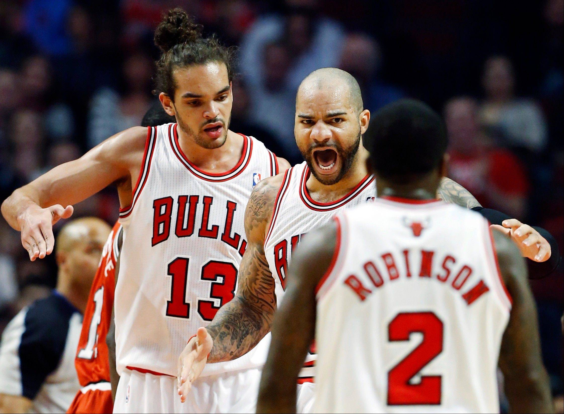Chicago Bulls forward Carlos Boozer, center, reacts as he celebrates with center Joakim Noah (13) and guard Nate Robinson (2) after scoring during the first half of an NBA basketball game against Wednesday the Milwaukee Bucks in Chicago.