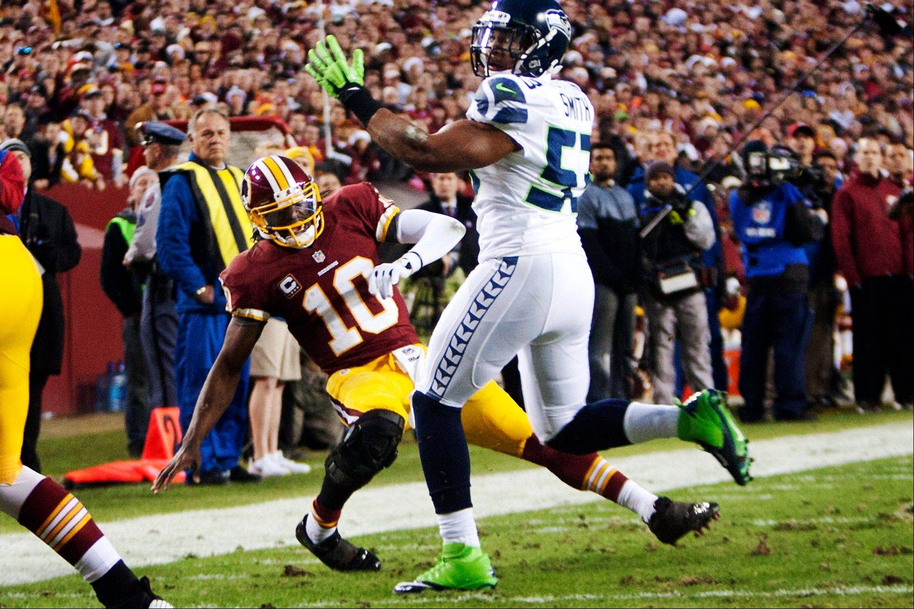 Washington Redskins quarterback Robert Griffin III (10) hurts his right knee as he falls awkwardly while throwing an incomplete pass under pressure from Seattle Seahawks linebacker Malcolm Smith (53) Sunday during the first quarter.