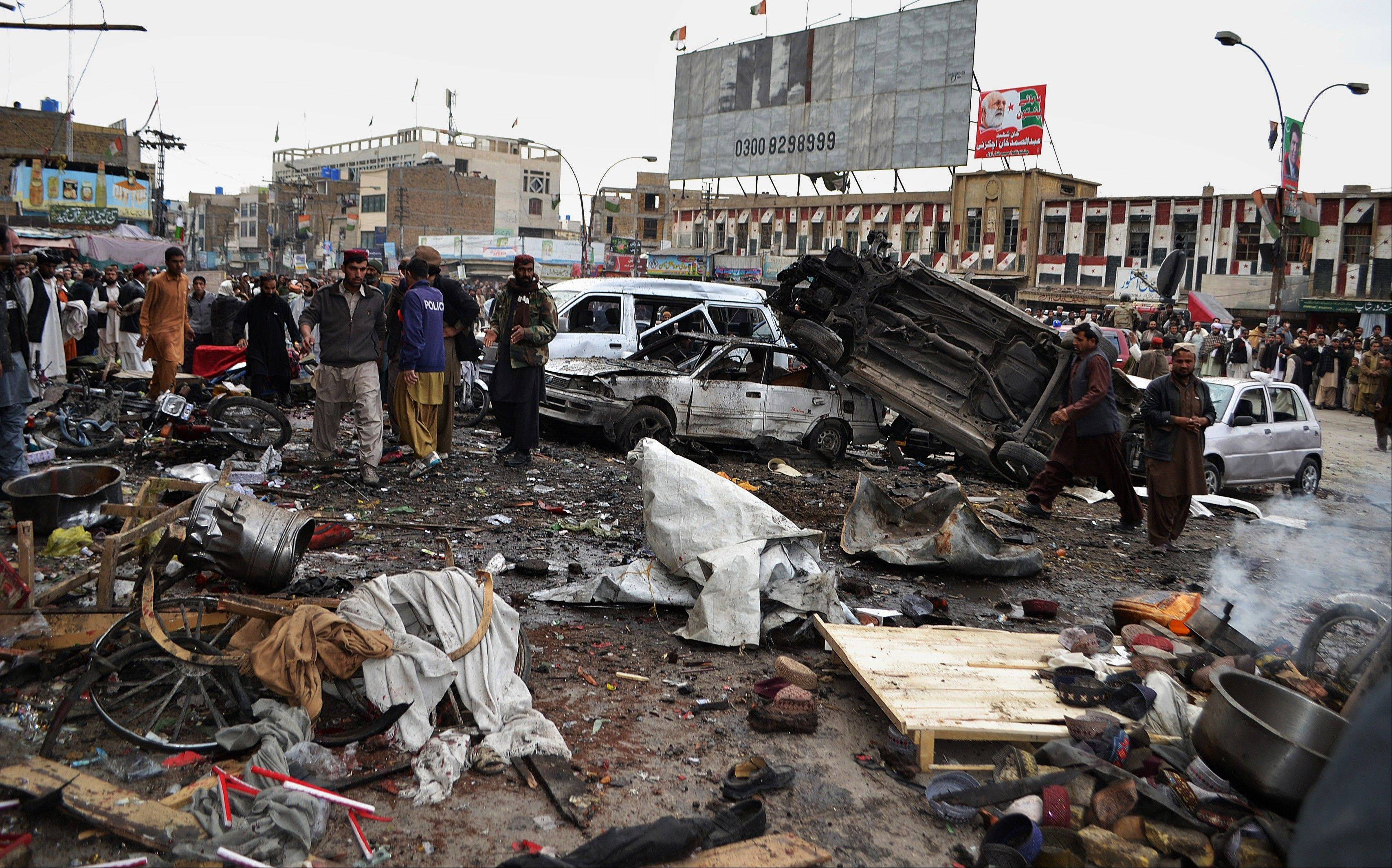 Pakistani police officers and local residents gather at the site of a bomb blast that targeted paramilitary soldiers in a commercial area in Quetta, Pakistan, killing at least 12 people and wounding more than 40 others, according to police, Thursday.