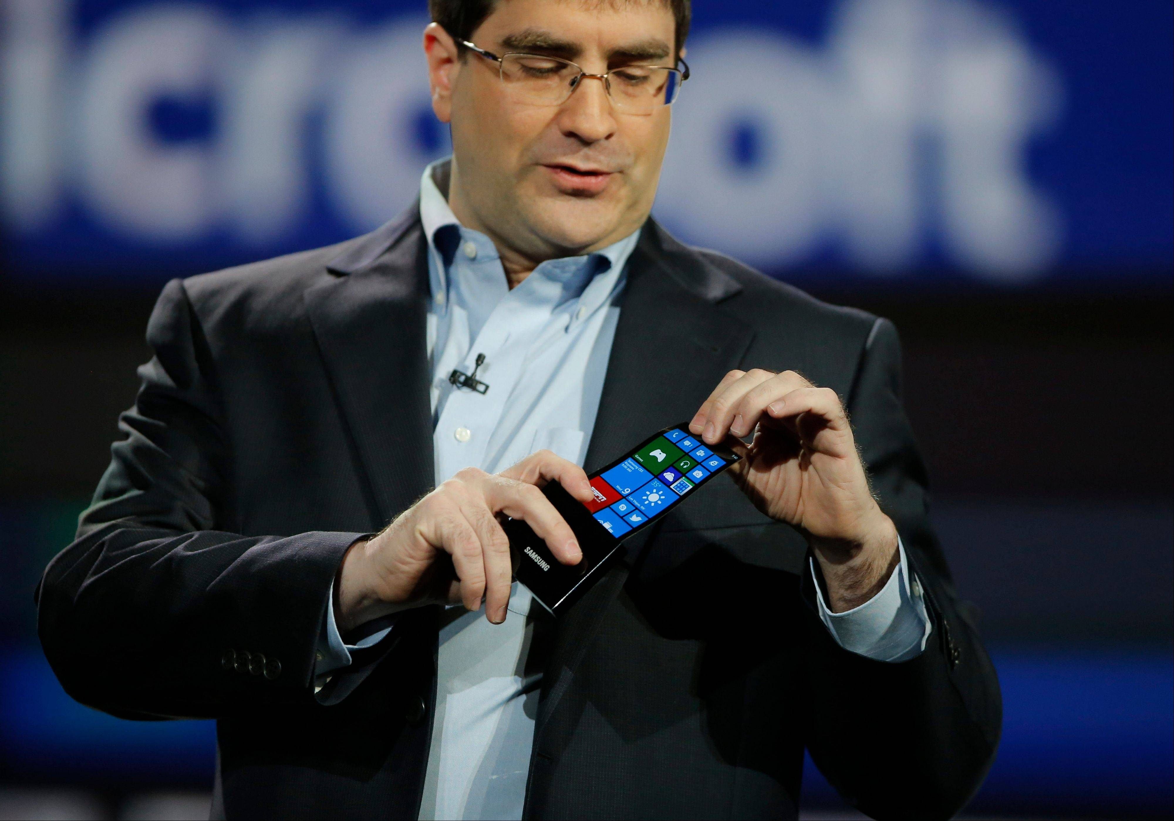 Eric Rudder, chief technical strategy officer of Microsoft, holds a prototype Windows smartphone with a flexible OLED display during Samsung's keynote address at the International Consumer Electronics Show in Las Vegas Wednesday.