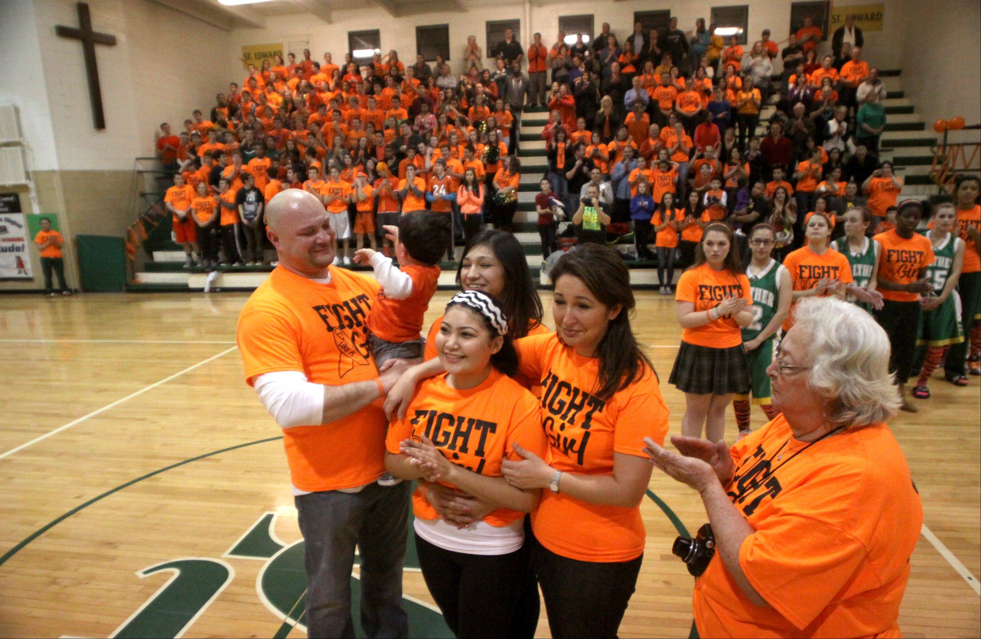 St. Edward sophomore basketball player Jordan Paz was honored before a varsity contest against Walther Lutheran at Elgin on Thursday night. Paz is undergoing treatment for Leukemia, and school personnel arranged an �Orange Out Night� to offer support. Fans donned orange shirts, and team members from both sides formed a receiving line for Paz and her family to enter center court amid cheers and a standing ovation.